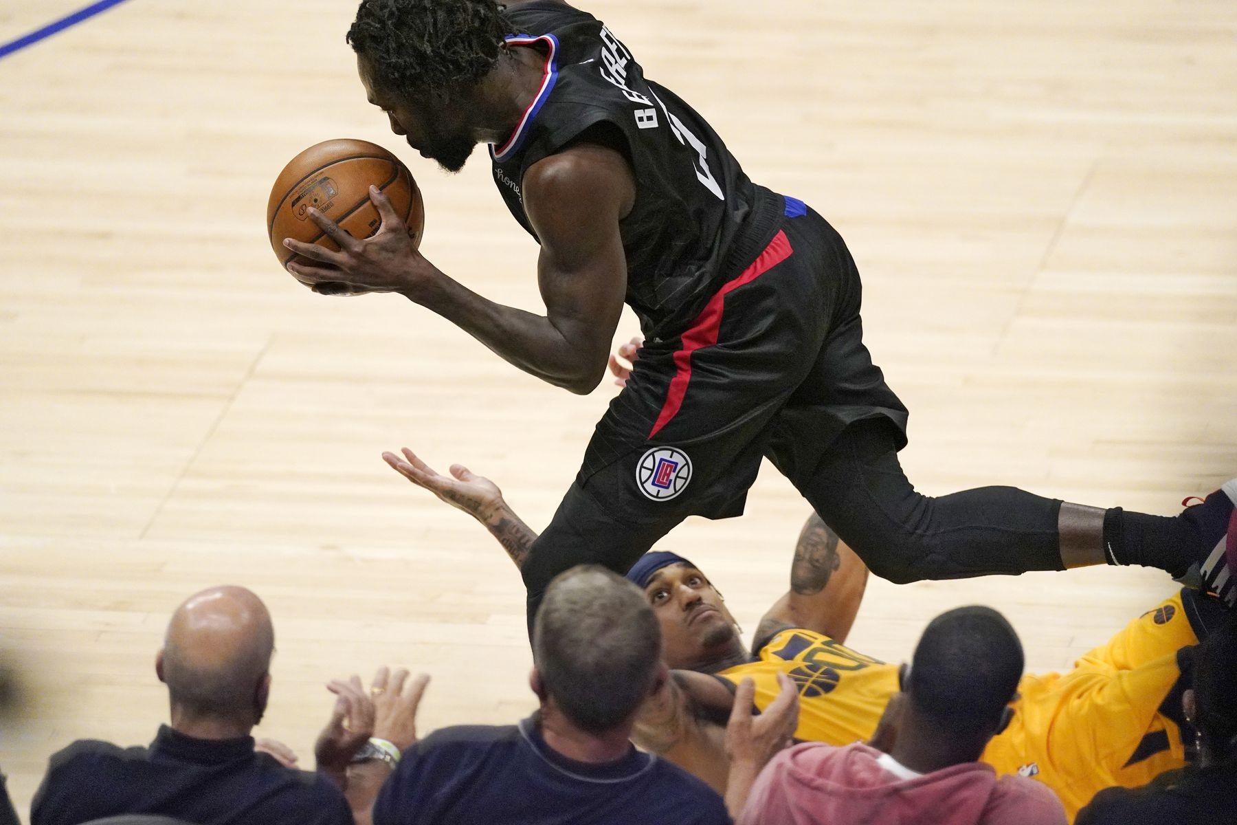 Los Angeles Clippers guard Patrick Beverley, top, dribbles as Utah Jazz guard Jordan Clarkson falls