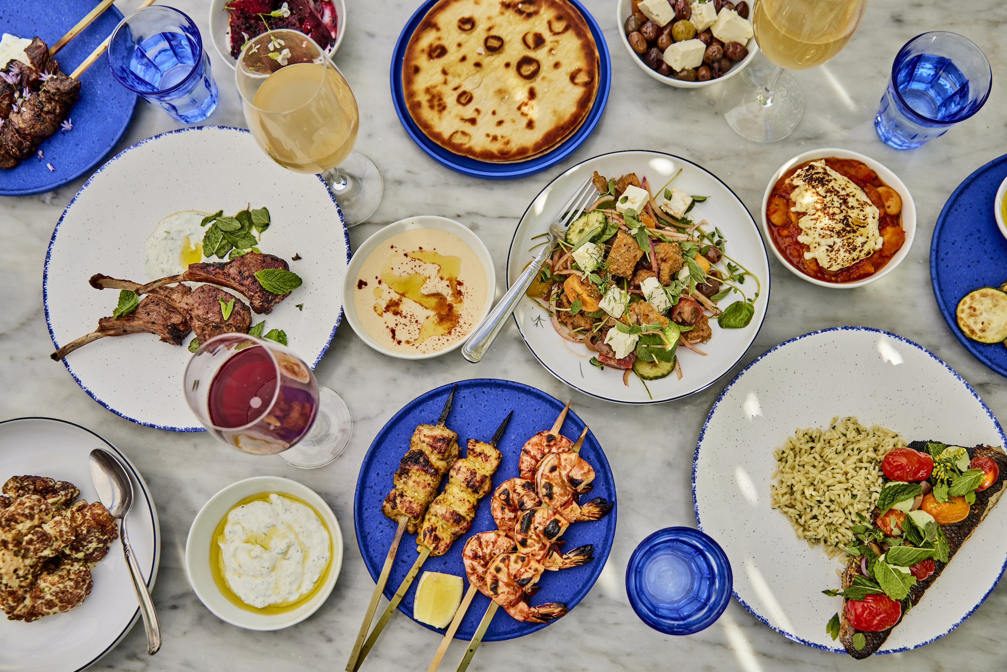 An overhead shot of Greek food on blue plates and a marble tabletop.