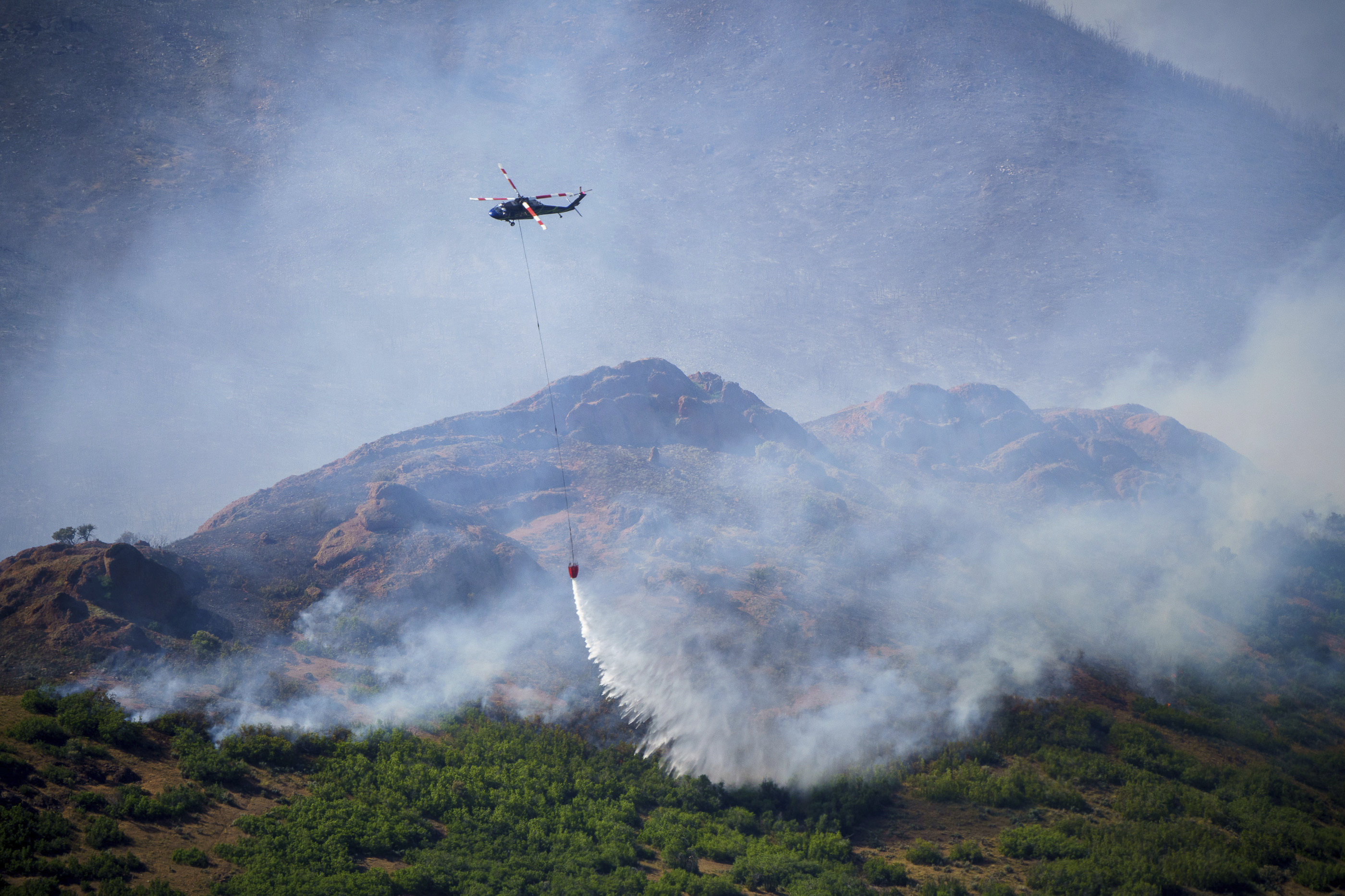 A helicopter drops fire retardant on the East Canyon Fire as it burns north of East Canyon State Park, on Tuesday, June 8, 2021, near Morgan, Utah.