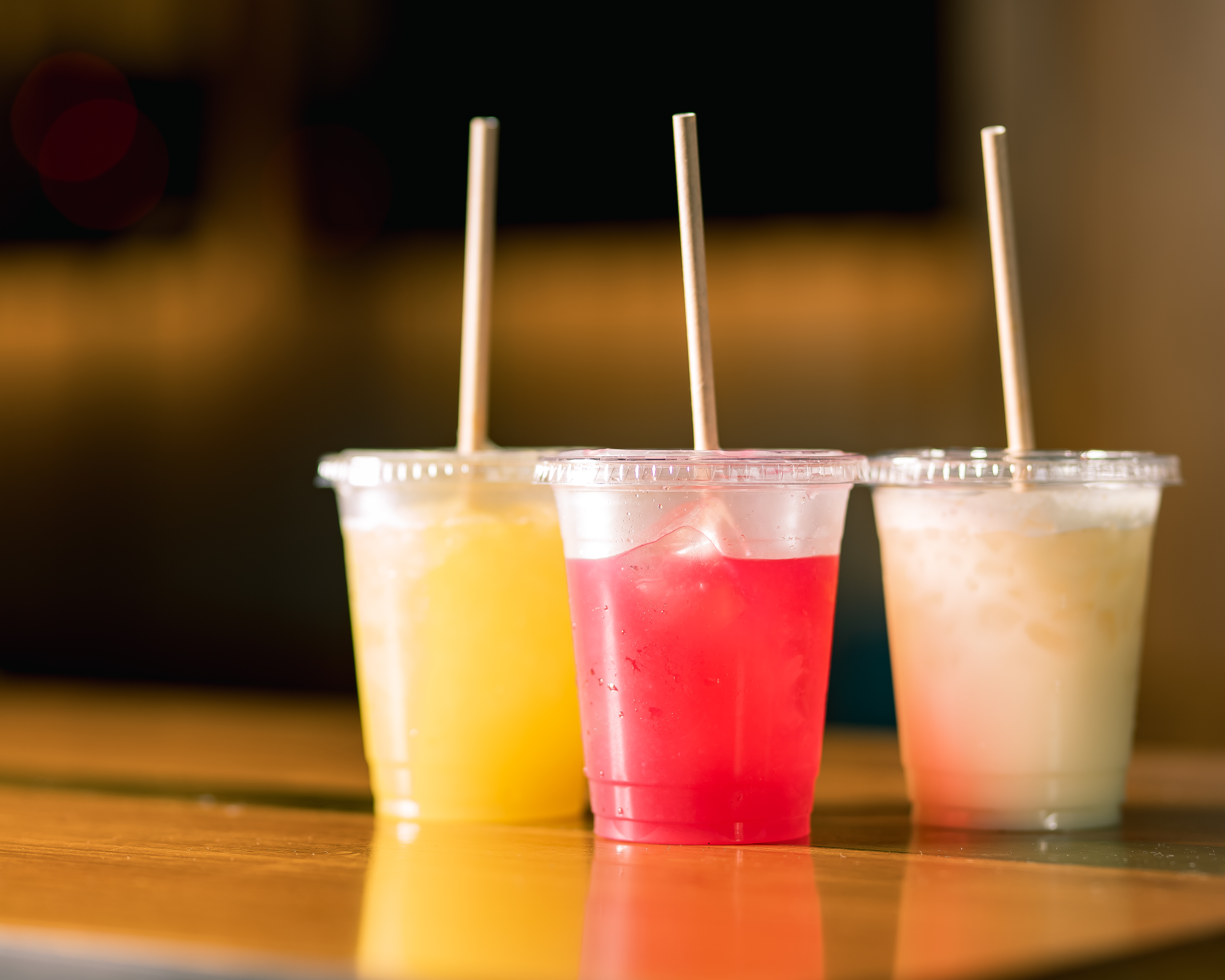 three clear plastic takeout cups with lids and straws, each filled with a different color drink