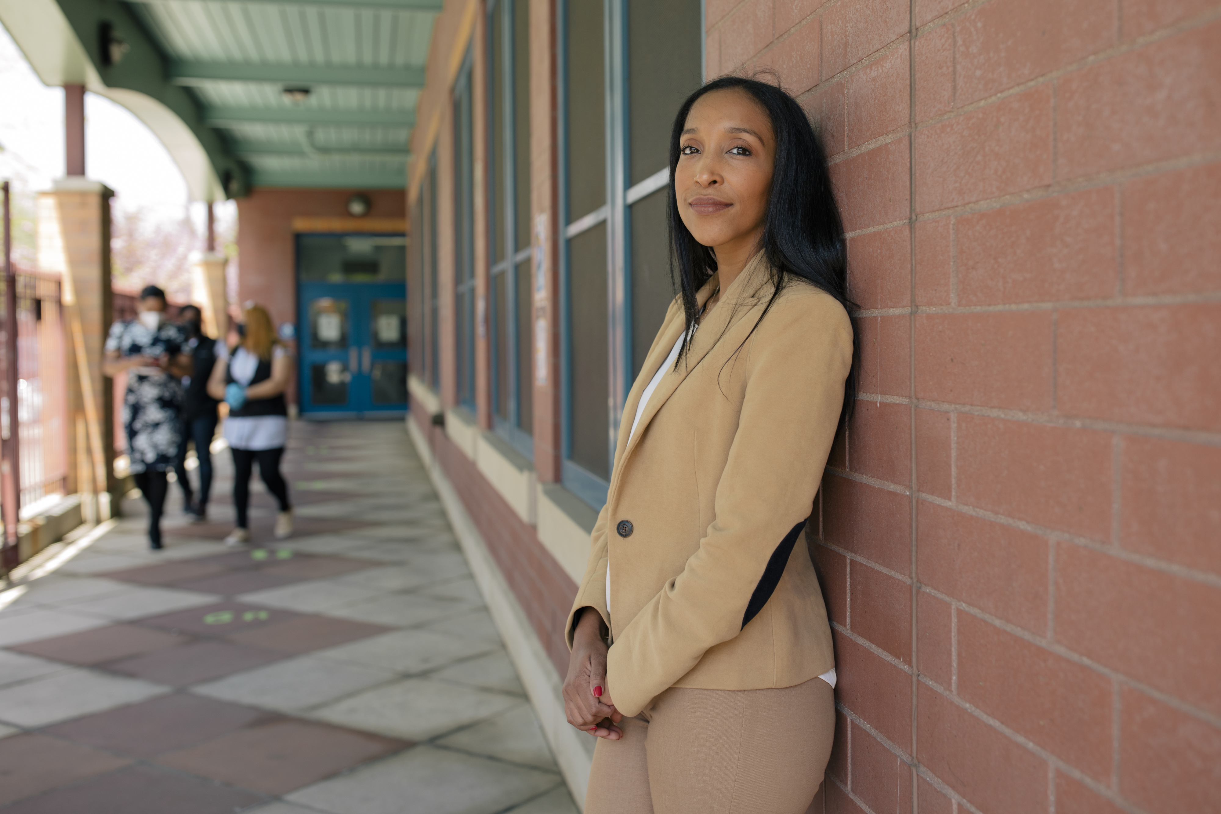 Yasirys Pichardo, wearing a tan pantsuit, stands against a red brick wall lined with windows while three women walk down the the path outside of P.S. 89.