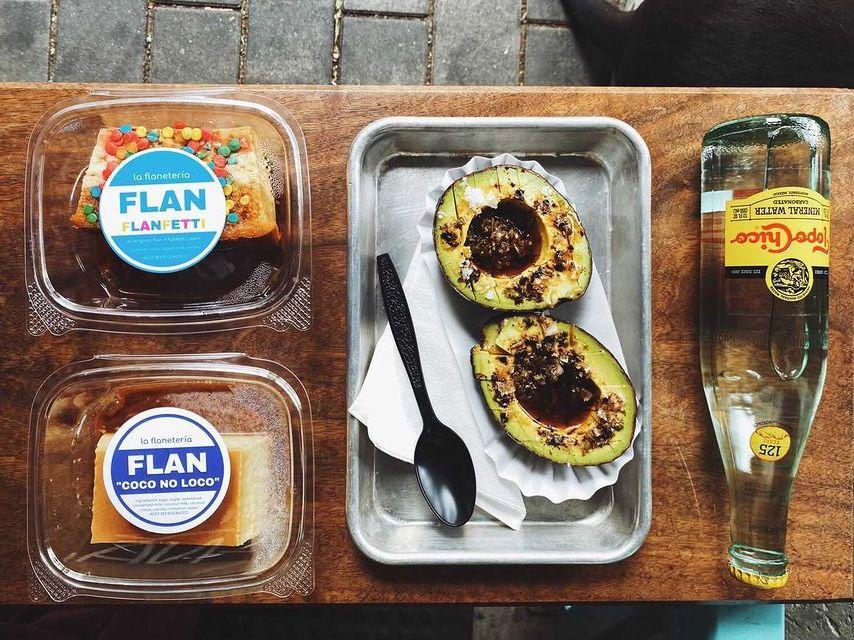一个狭窄的木桌在石头表面上方的俯视视图。在桌子上,有两个塑料包装,每个都有一片果馅饼,金属托盘上有一个对半的鳄梨,上面淋着深色的酱汁,还有一瓶Topo Chico