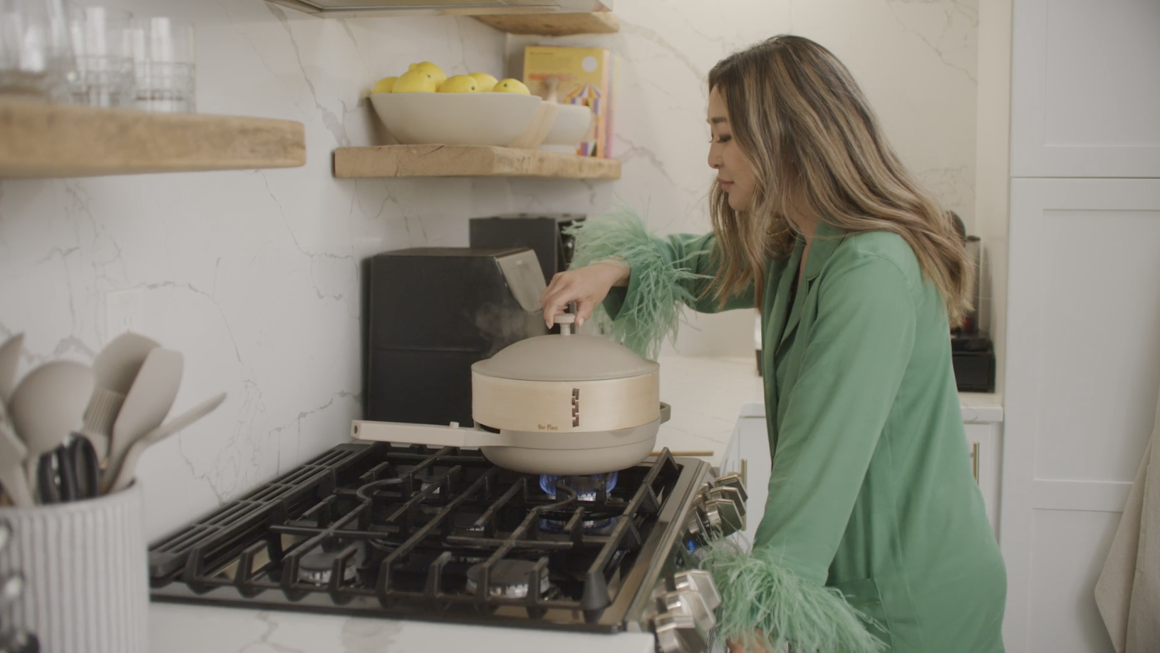 A woman wearing green pajamas leaning over a stovetop, lifting the lid of a pan.