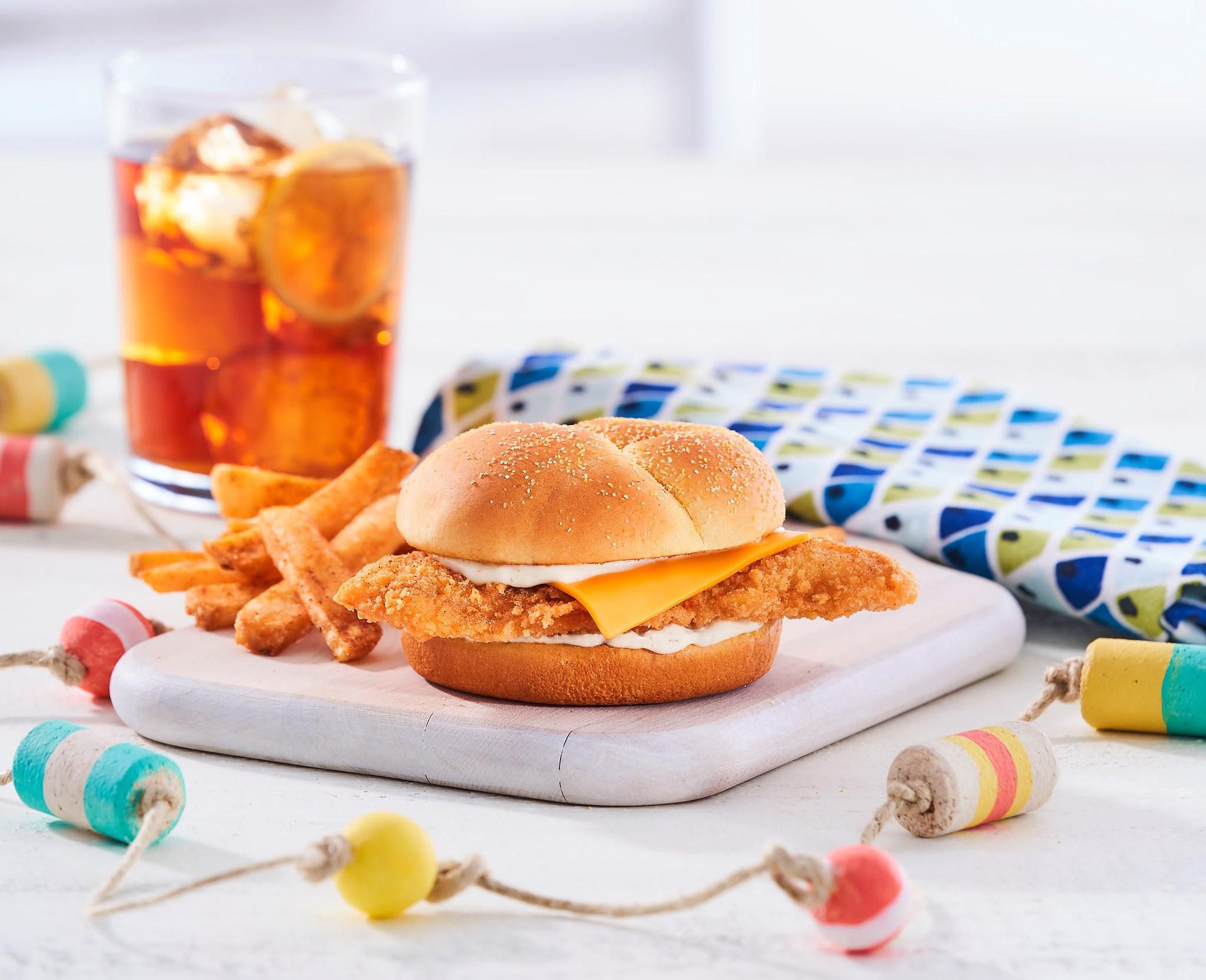 一块炸鸡三明治放在白板上,背景是调味薯条和冰茶