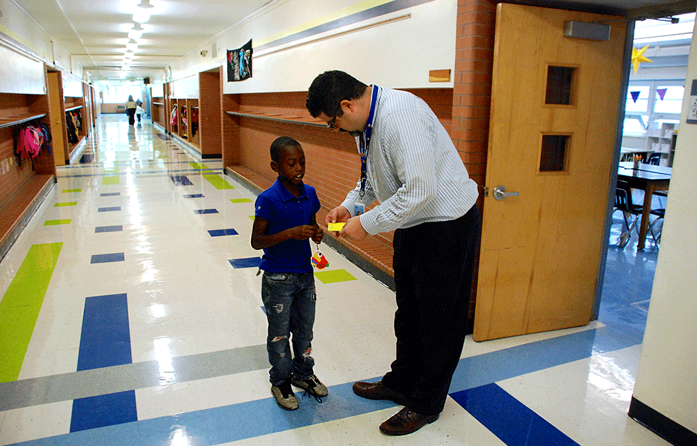 In a school hall, an elementary principal bends down to look at a student's hall pass.