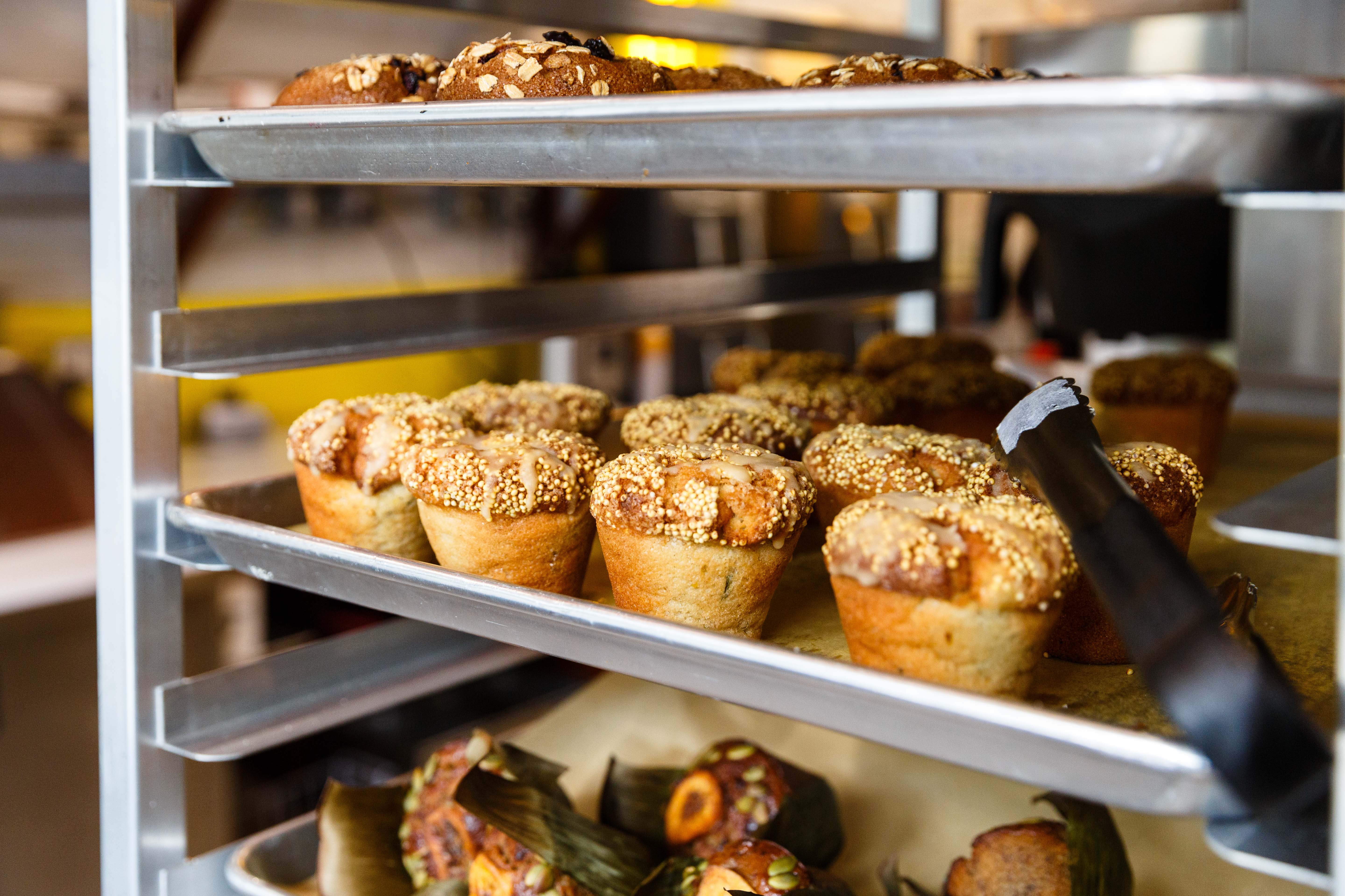 Three trays of muffins rest on a multi-tiered baking tray in a restaurant
