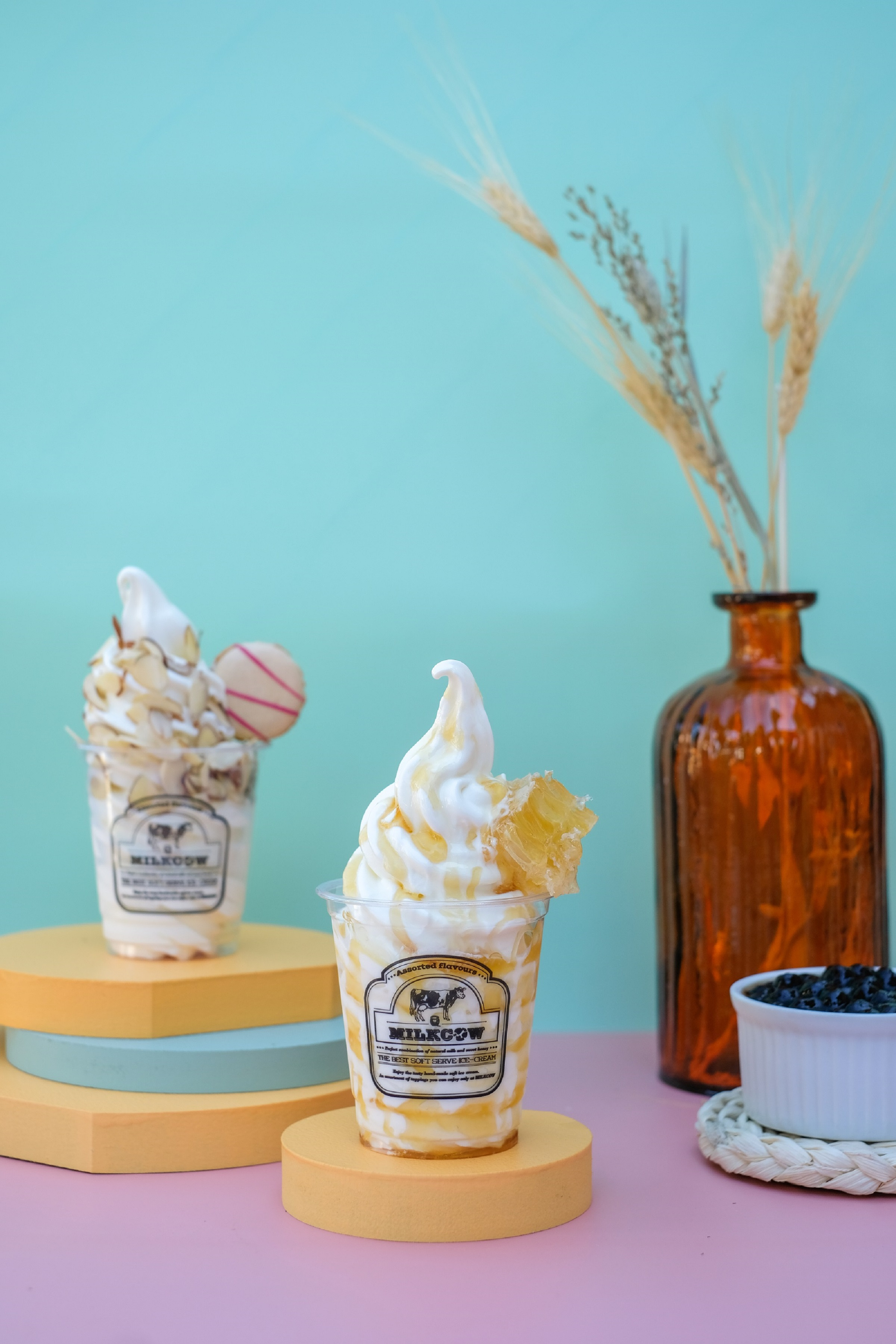 Two soft serve ice creams in a cup topped with a macaron on one and honeycomb on the other. A brown glass bottle sits on the right.
