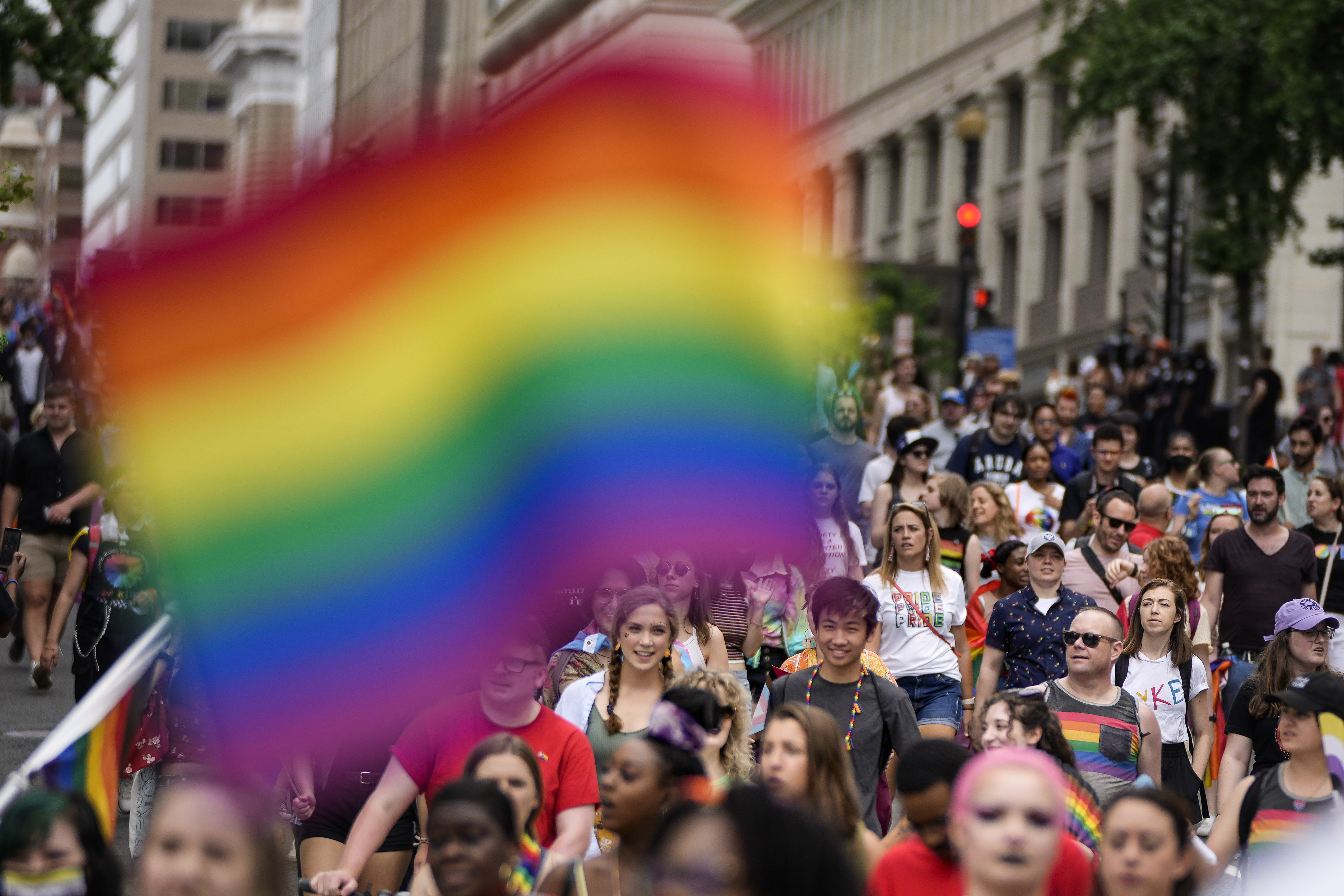 A huge crowd of people march down a city street as a Pride flag hangs in the foreground.