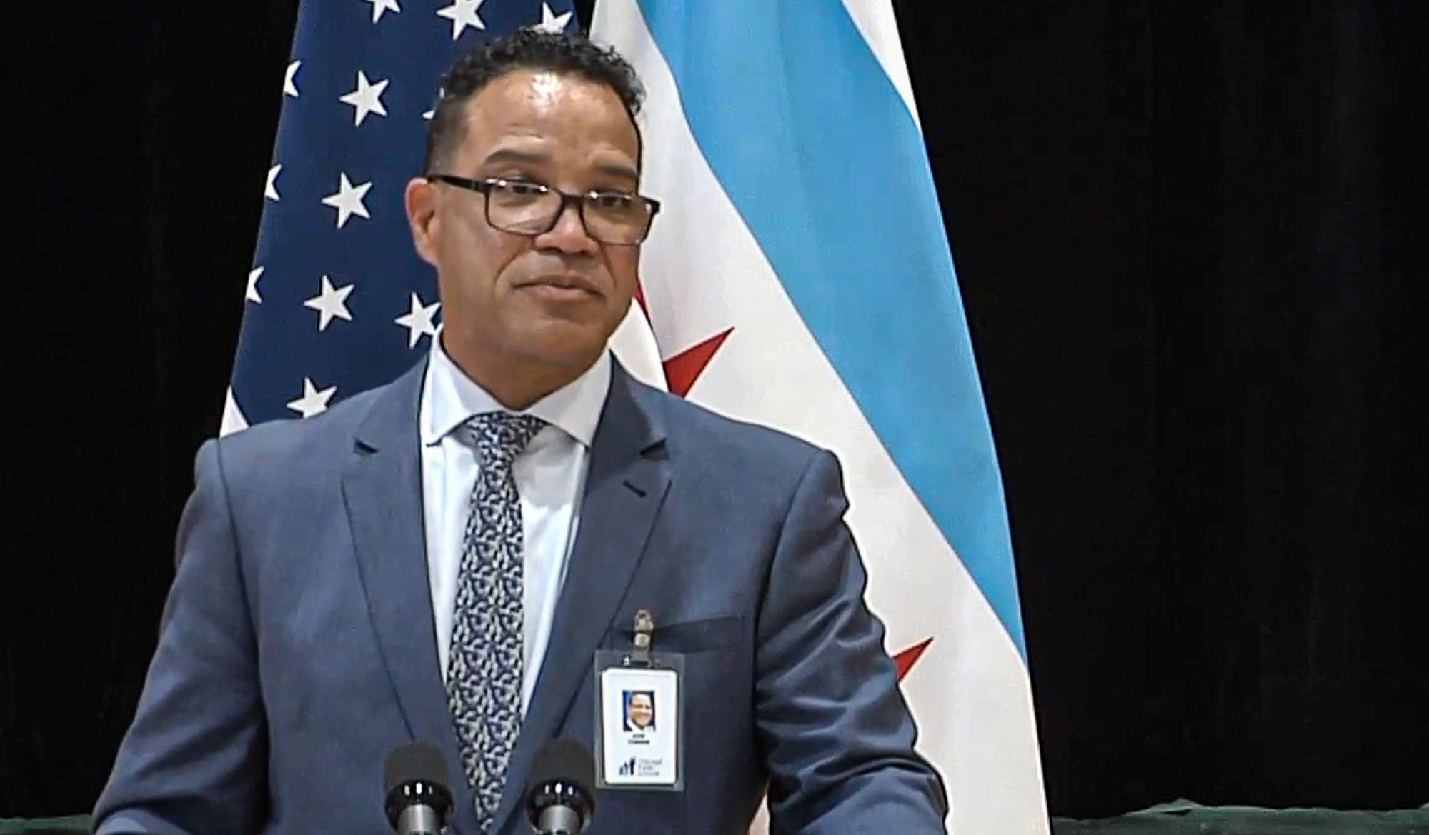 Dr. JoséTorres speaks at a podium in front of the flags of the United States and Chicago.