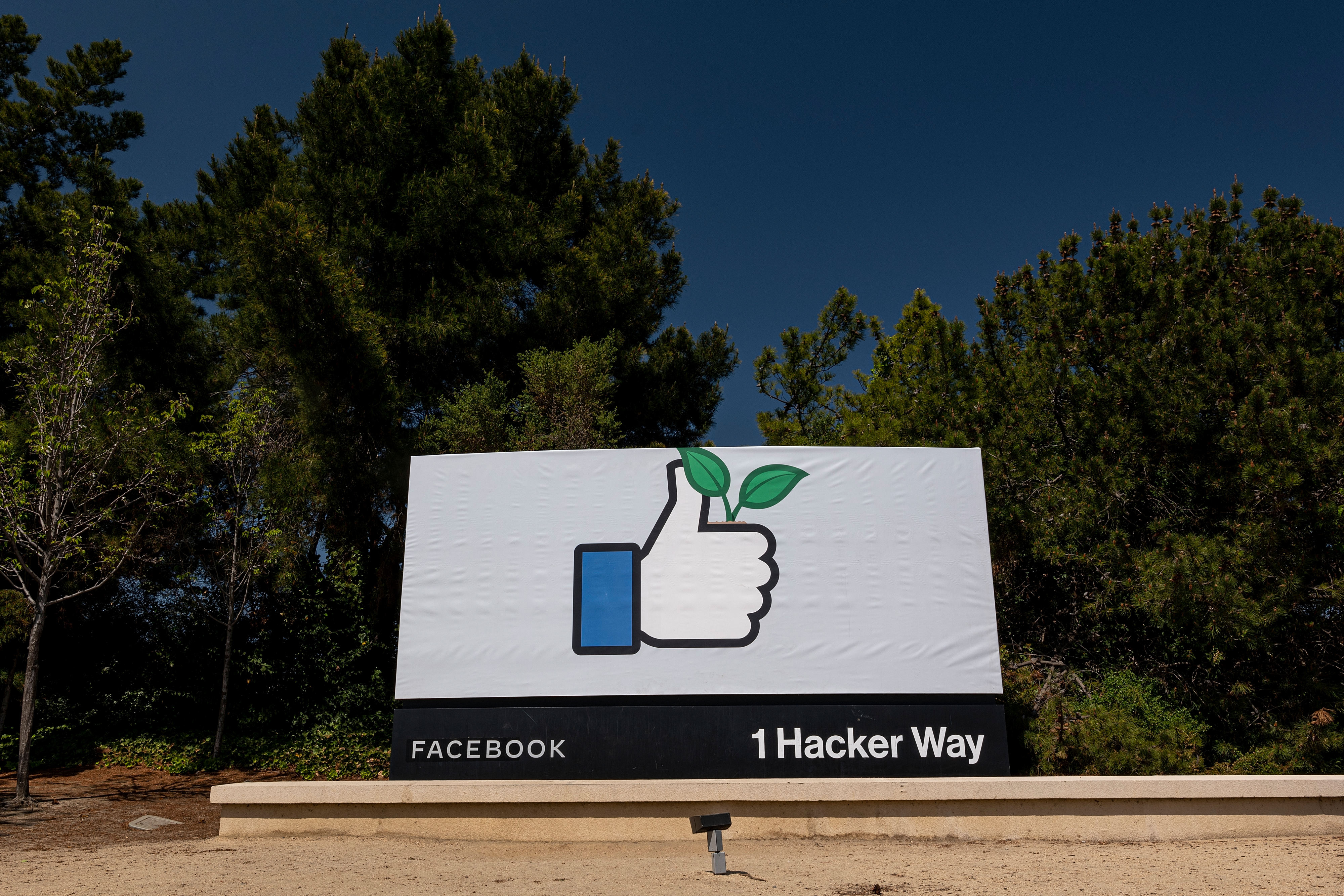 The Facebook sign at 1 Hacker Way shows a thumbs-up icon holding a plant sprout.