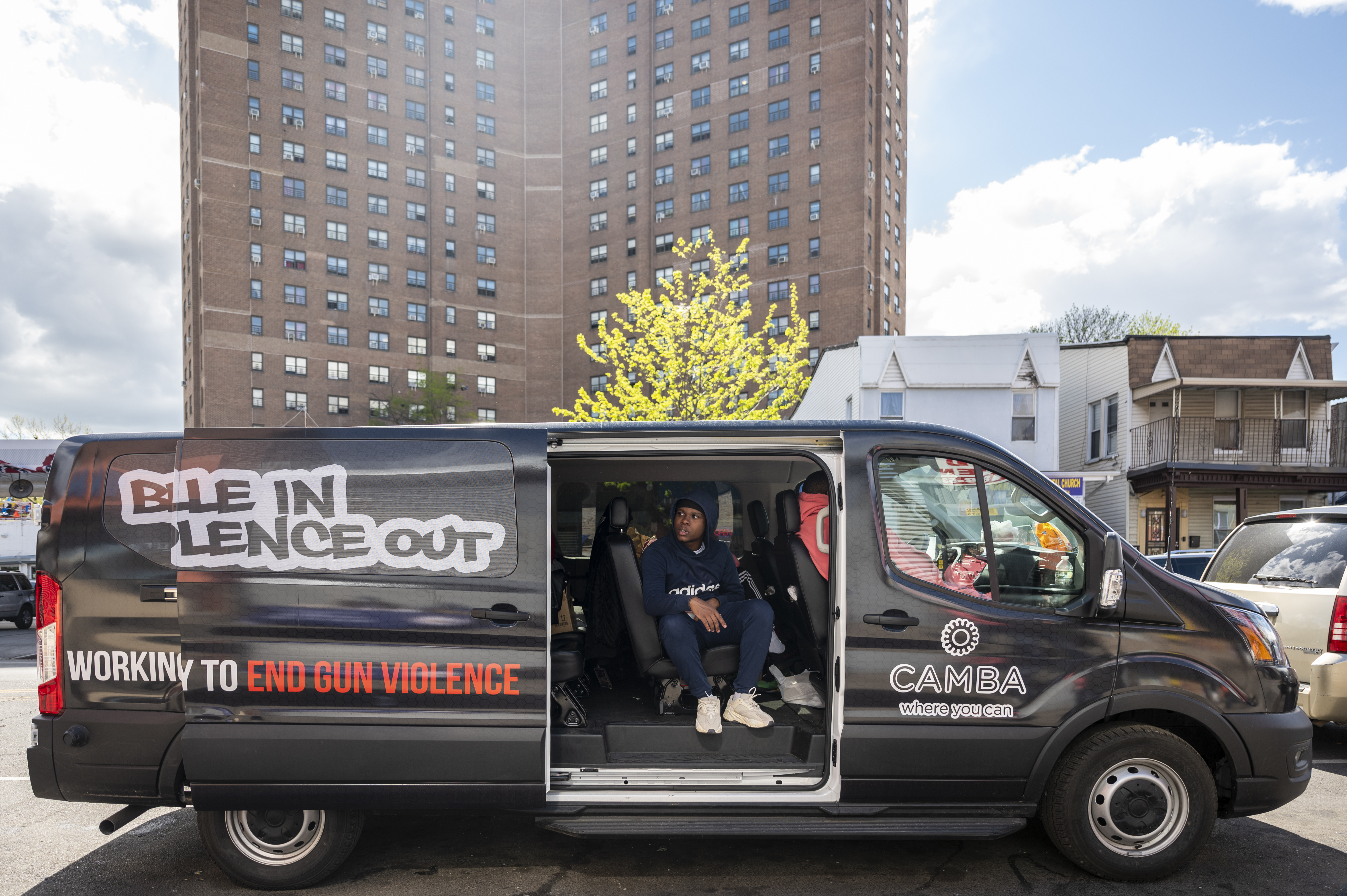 """A van with the cure-violence group """"Brownsville In Violence Out"""" sits near the intersection of Sutter Avenue and Mother Gaston Boulevard as the Langston Hughes Houses tower in the background, on Friday, Apr. 30, 2021."""