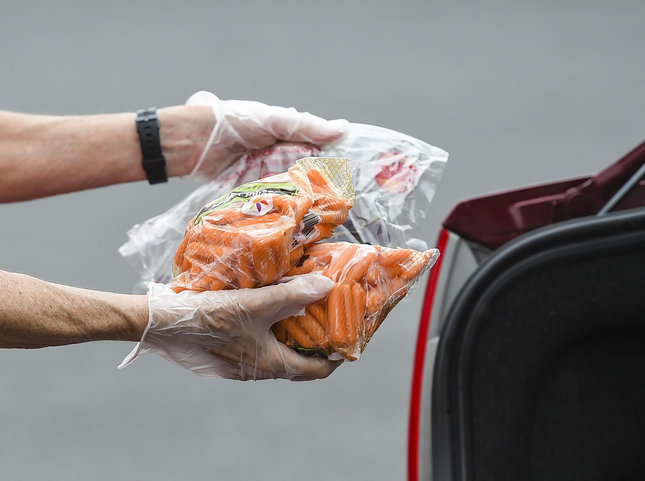"""一名志愿者拿着一袋袋的胡萝卜,她要把这些胡萝卜送给一个在""""帮助收获移动市场""""的人。2021年6月2日星期三下午,奥利镇的奥利集市上的一个帮助收割移动市场"""
