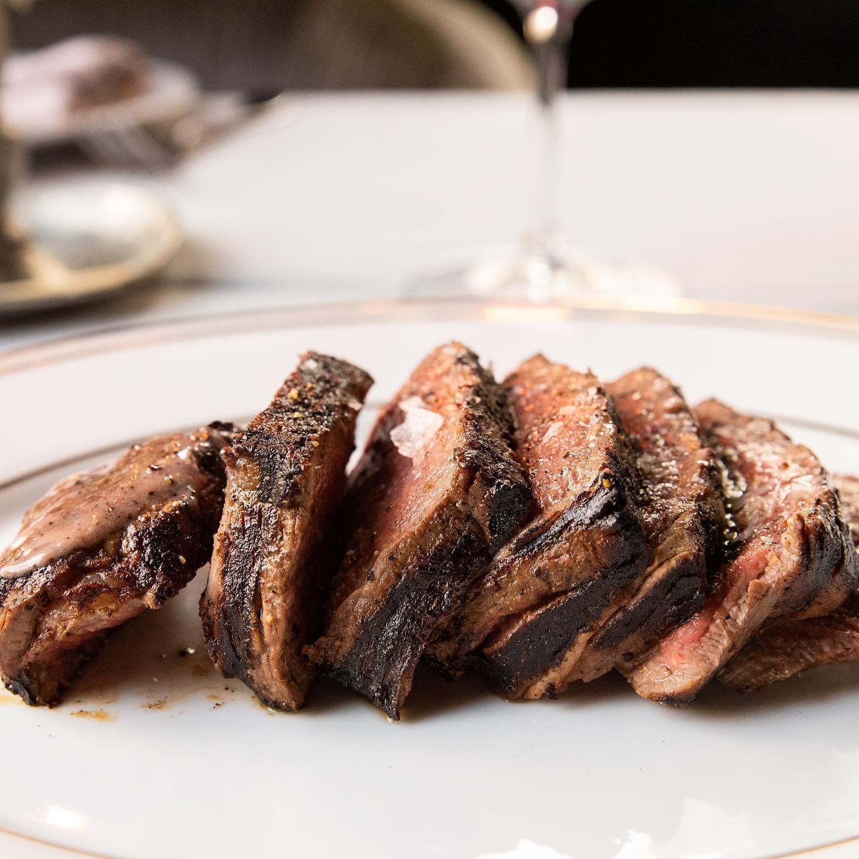 一块切成圆形的牛排,放在桌上,配有酒杯和白桌布