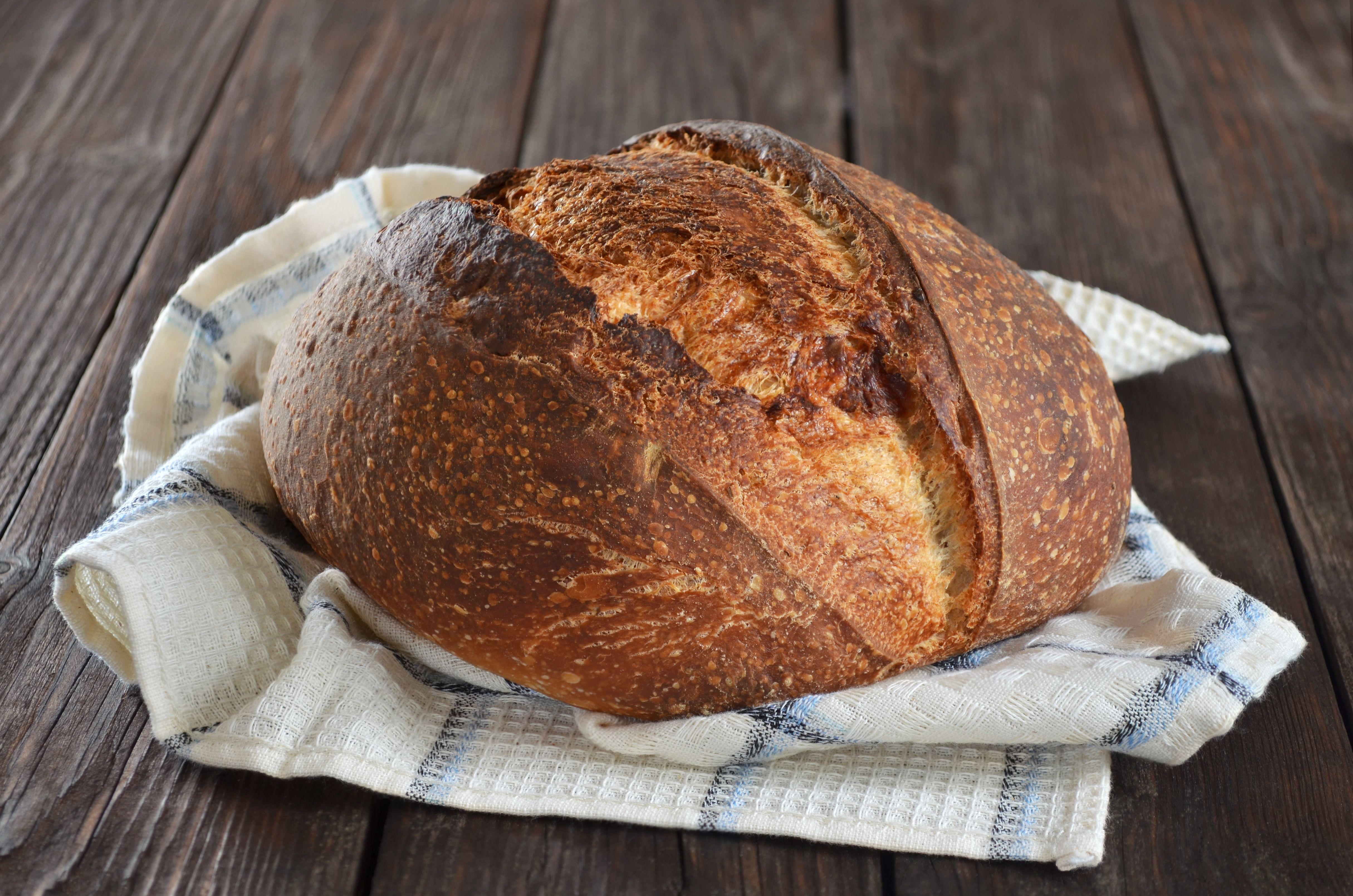 一块白格子毛巾上的未切的酸面包。