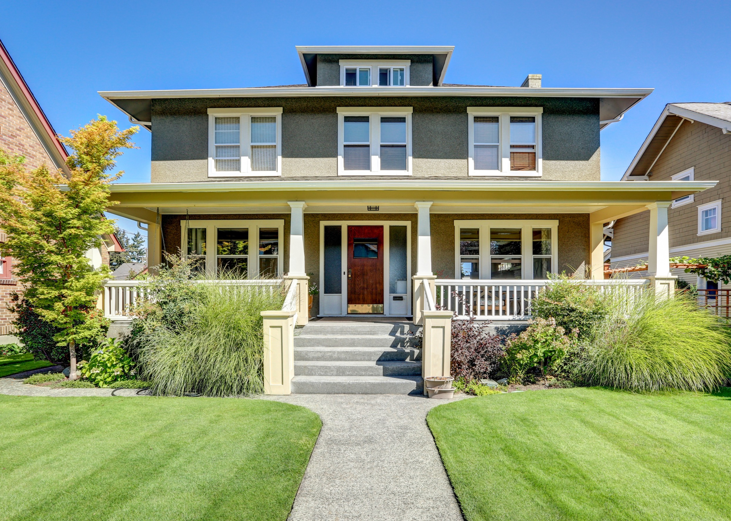 A dark green craftsman style home with wood front door, large front porch, bright green yard, and large shrubs