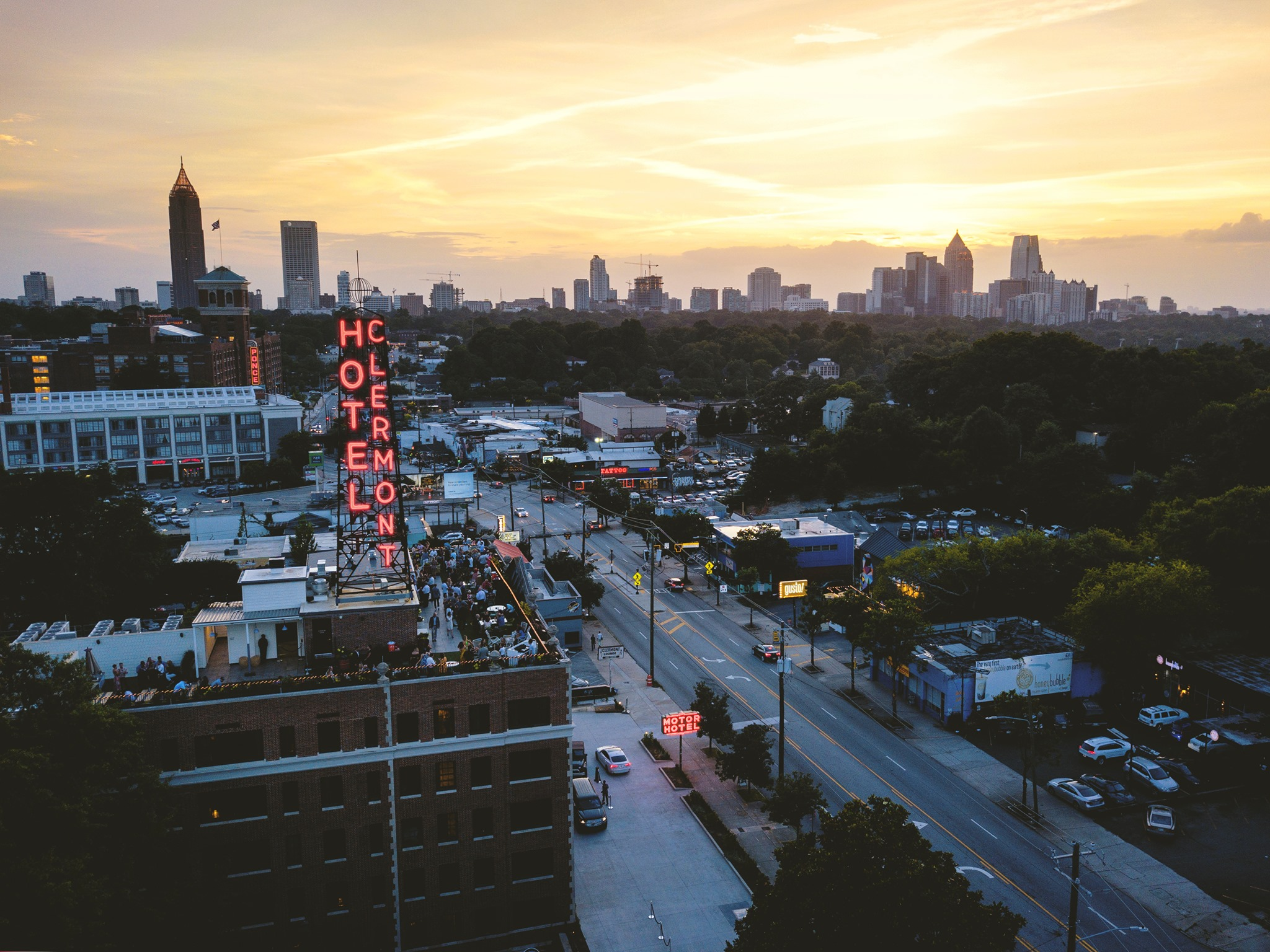An aerial overlooking the rooftop filled with people at the bar of the Hotel Clermont on dusk with the Atlanta skyline backlit by the setting sun in the distance