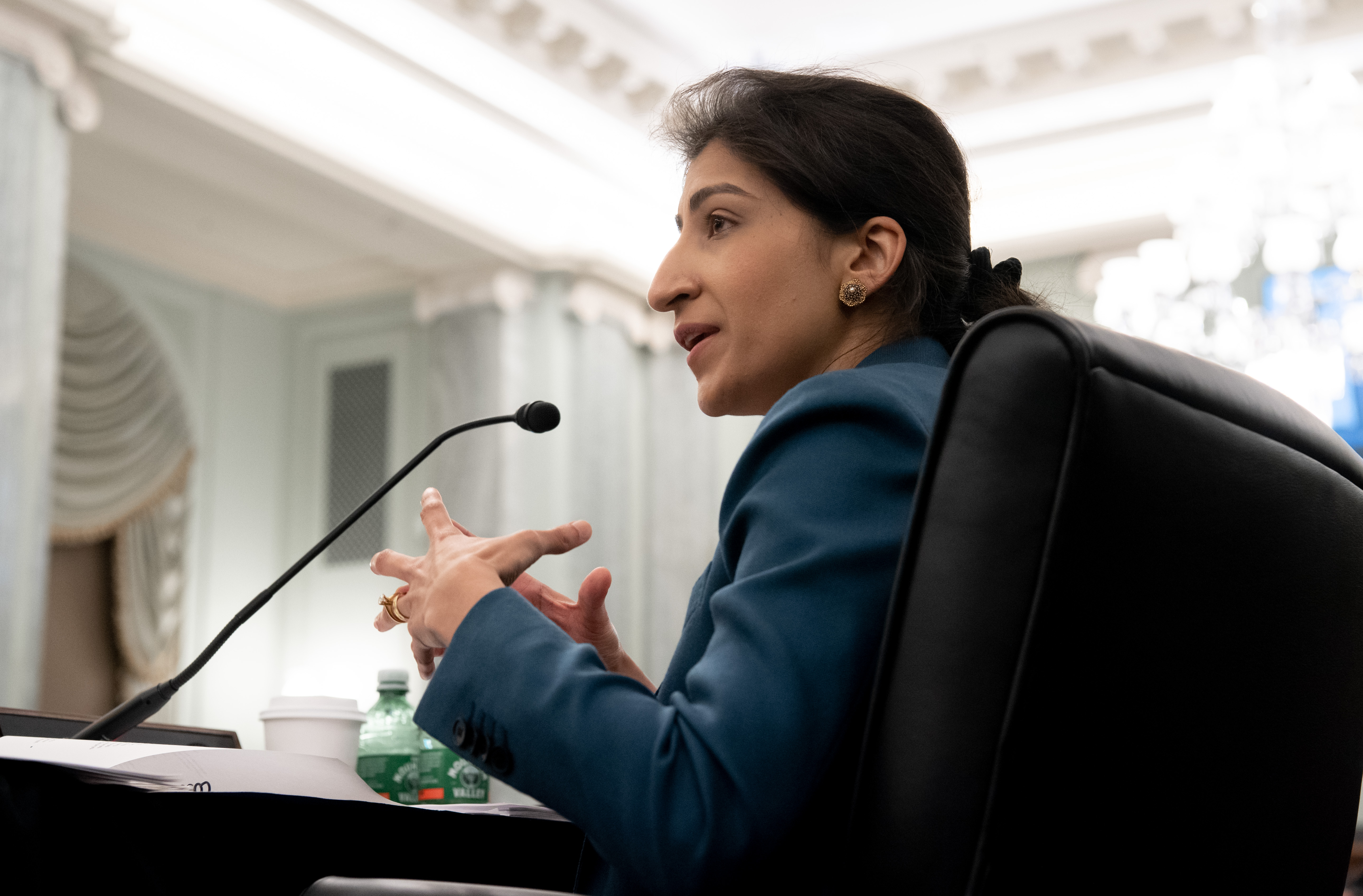 Lina Khan speaking into a microphone at a congressional hearing.