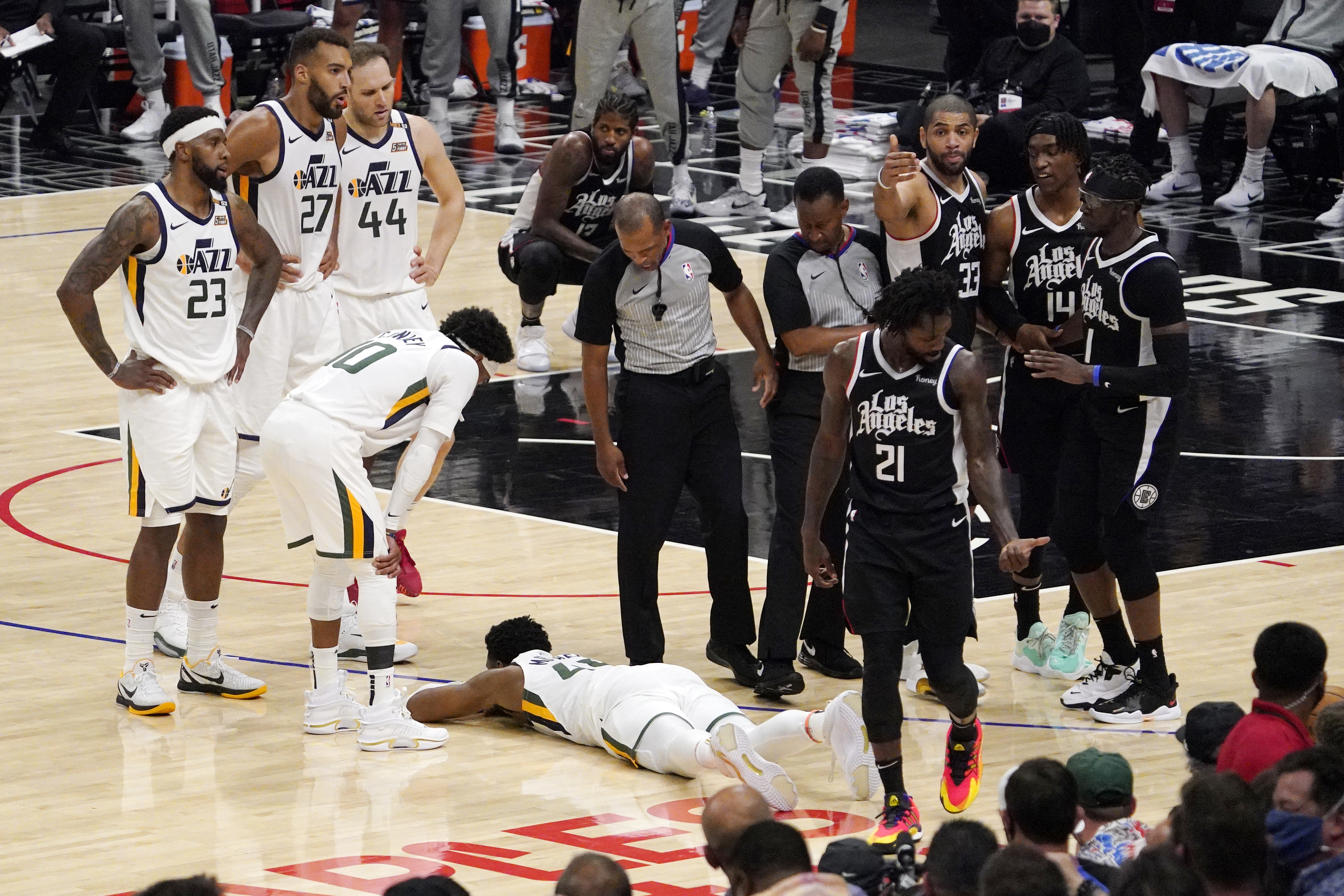 Utah Jazz guard Donovan Mitchell lays on the court, surrounded by members of the Utah Jazz and Los Angeles Clippers