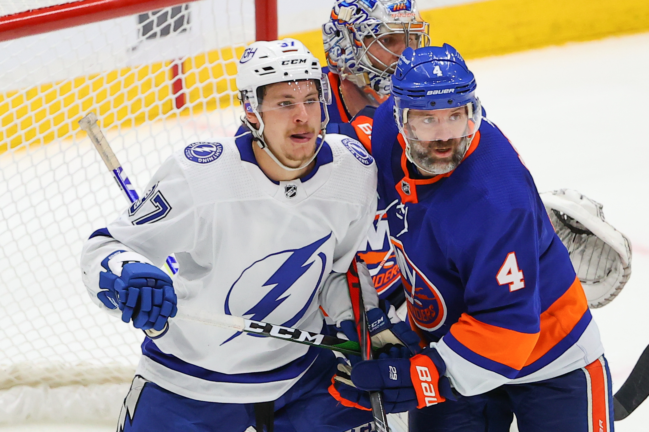 Tampa Bay Lightning center Yanni Gourde (37) battles New York Islanders defenseman Andy Greene (4) during the third period of the National Hockey League Stanley Cup Playoff Semifinal game between the New York Islanders and the Tampa Bay Lightning on June 17,2021 at Nassau Veterans Memorial Coliseum in Uniondale,NY.