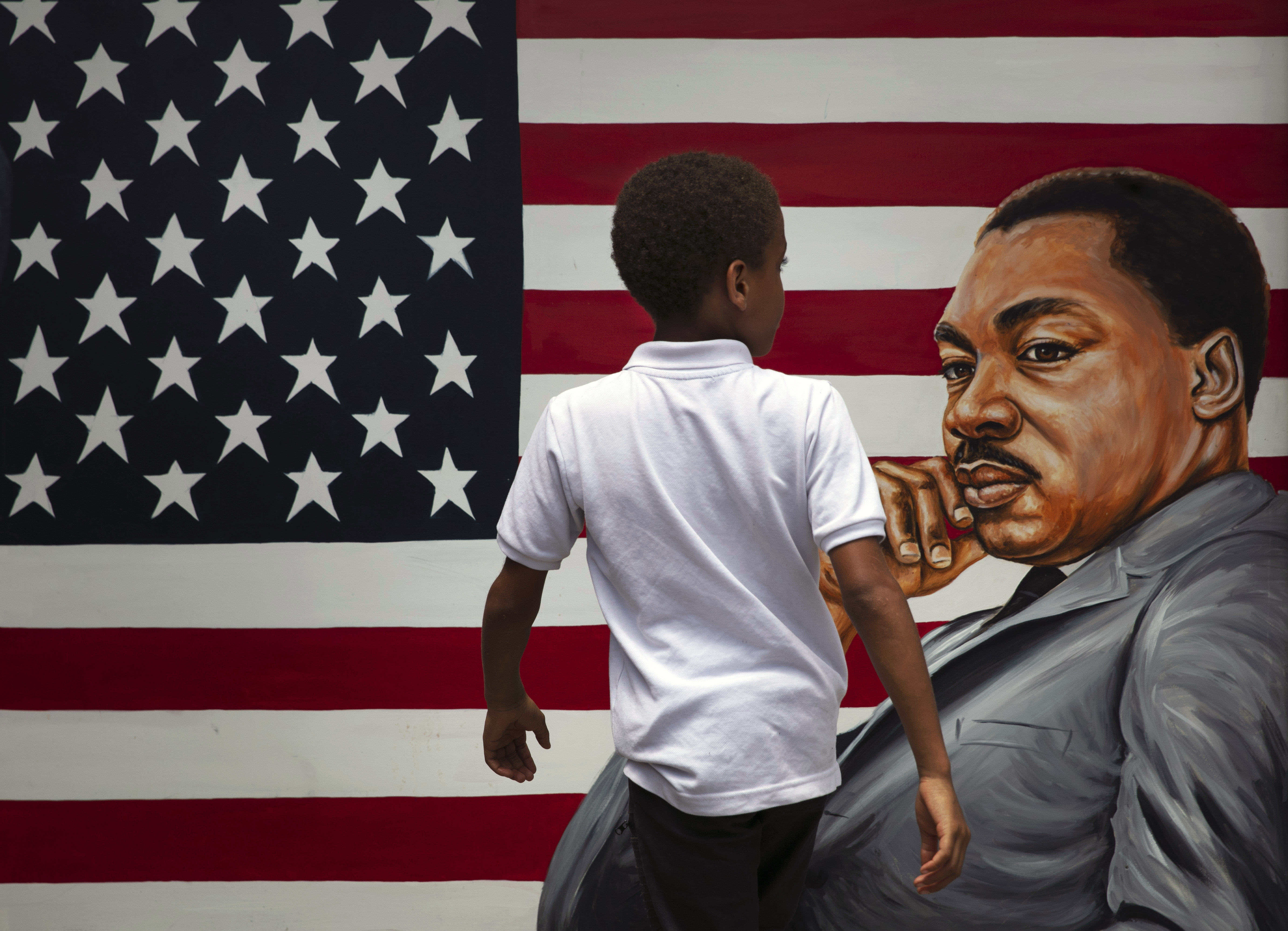 A young boy walks past a painting depicting Dr. Martin Luther King Jr. during a Juneteenth celebration in Los Angeles.