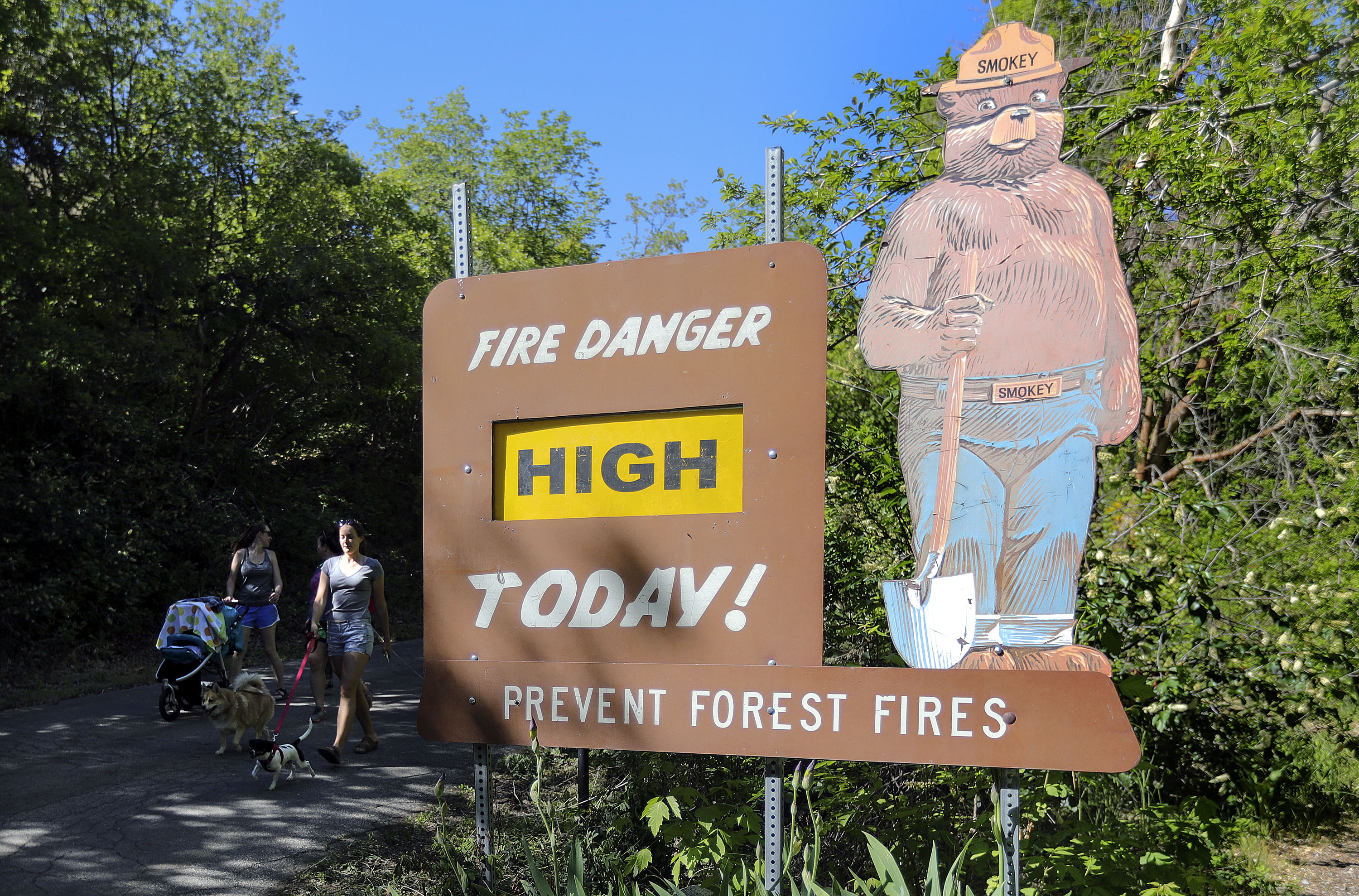 """A fire danger sign is shown reading """"High"""" in City Creek Canyon in Salt Lake City as two people walk by."""