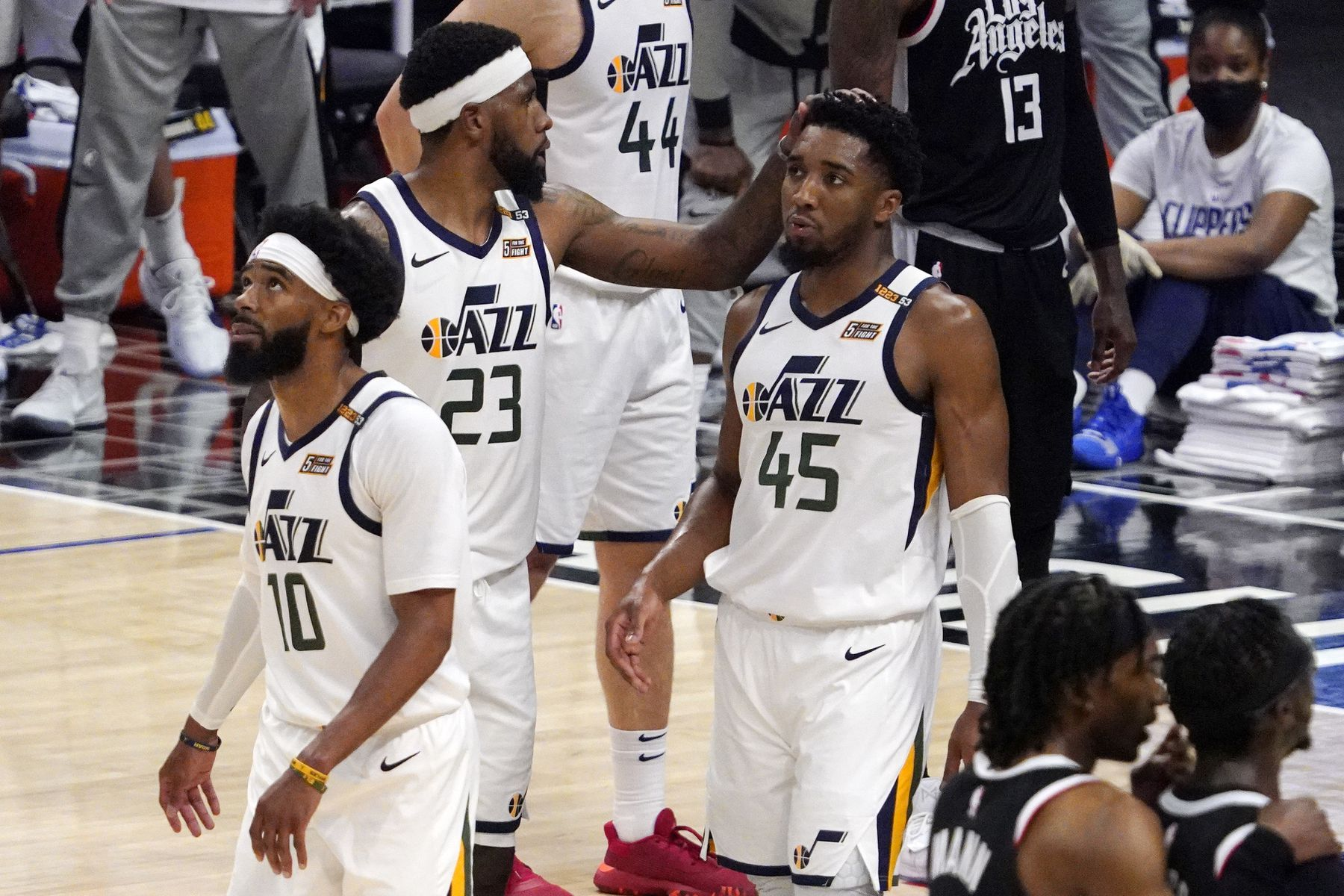 Utah Jazz forward Royce O'Neale, center, pats guard Donovan Mitchell, right, on the head as guard Mike Conley walks away
