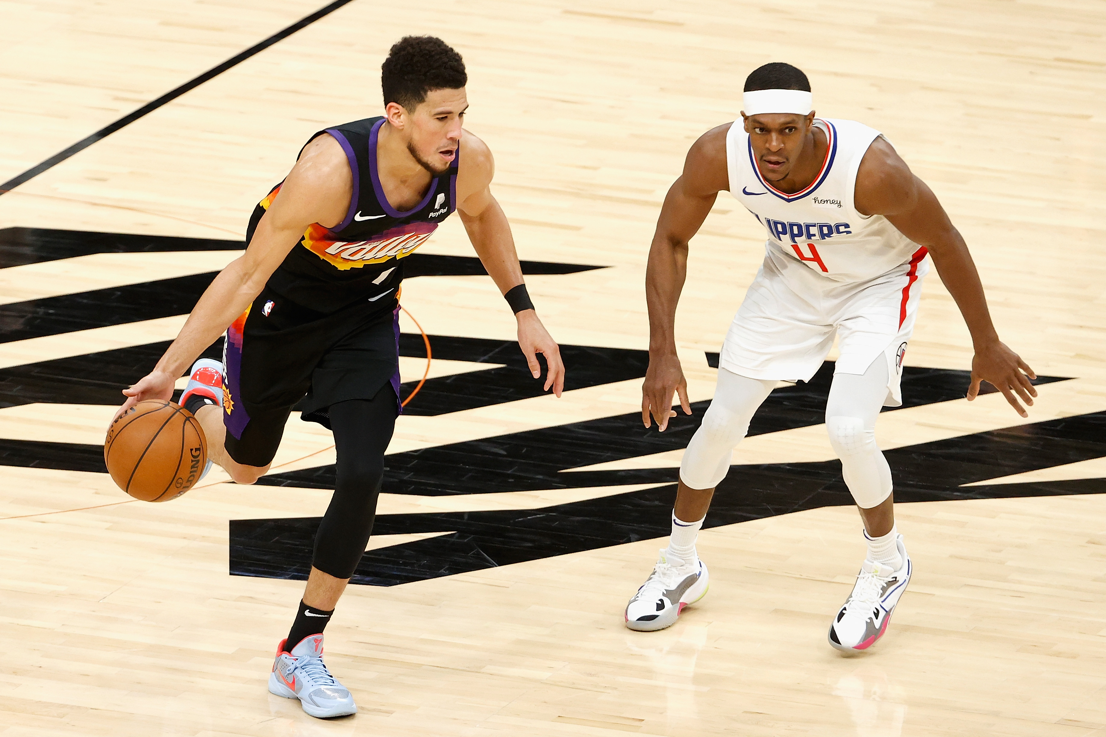 Devin Booker of the Phoenix Suns handles the ball against Rajon Rondo of the LA Clippers during the NBA game at Phoenix Suns Arena on April 28, 2021 in Phoenix, Arizona. The Suns defeated the Clippers 109-101.