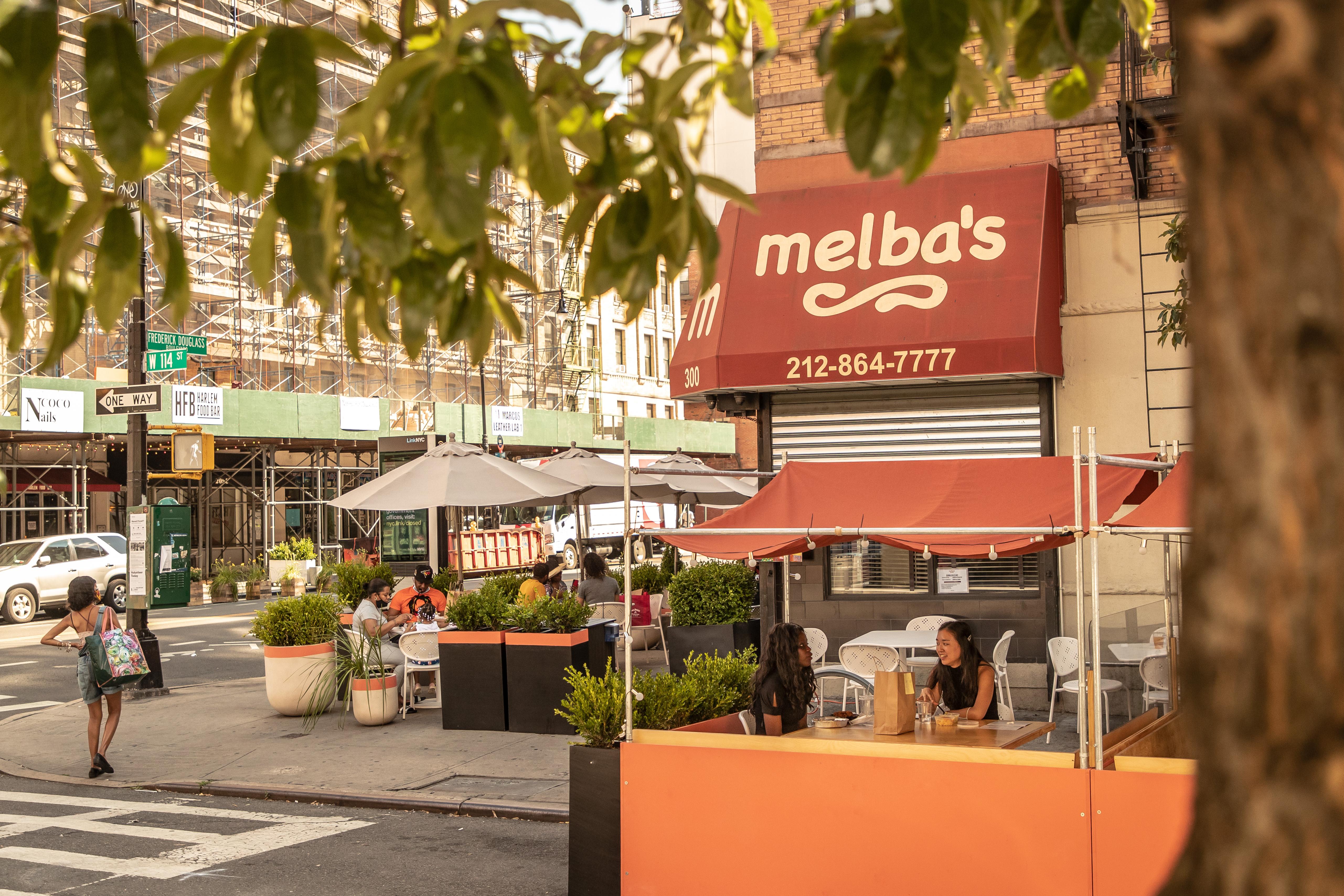 顾客们在Melba餐厅外面,在橙色的遮阳篷下用餐