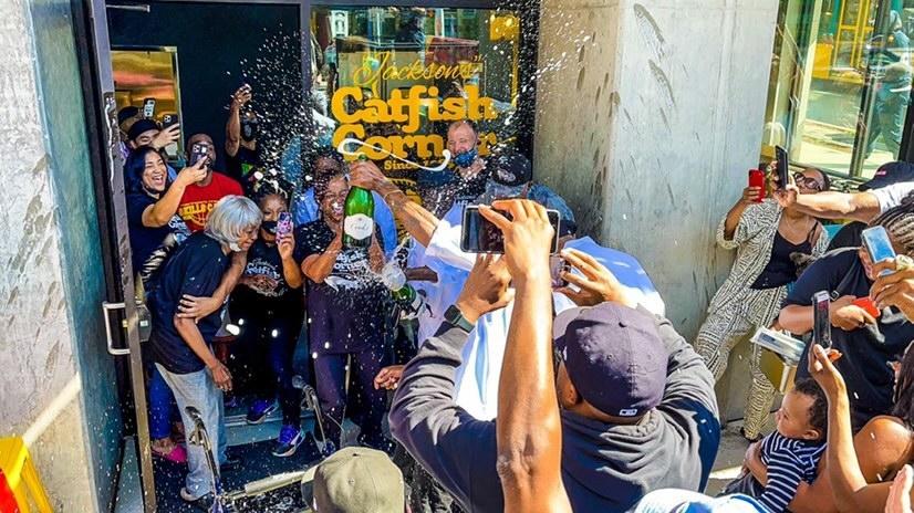 一群人在中央区杰克逊街的杰克逊的鲶鱼角外的香槟秀。