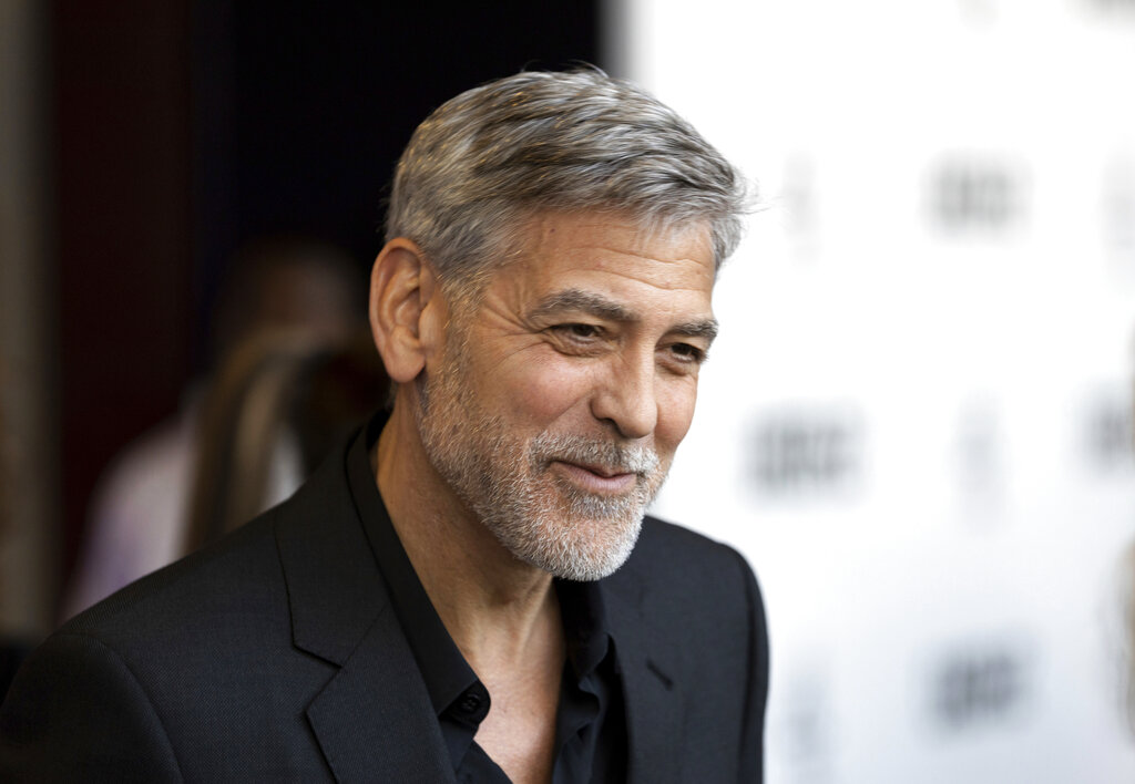 """Actor George Clooney talks to reporters on arrival at the premiere of the television mini-series """"Catch22,"""" in London."""