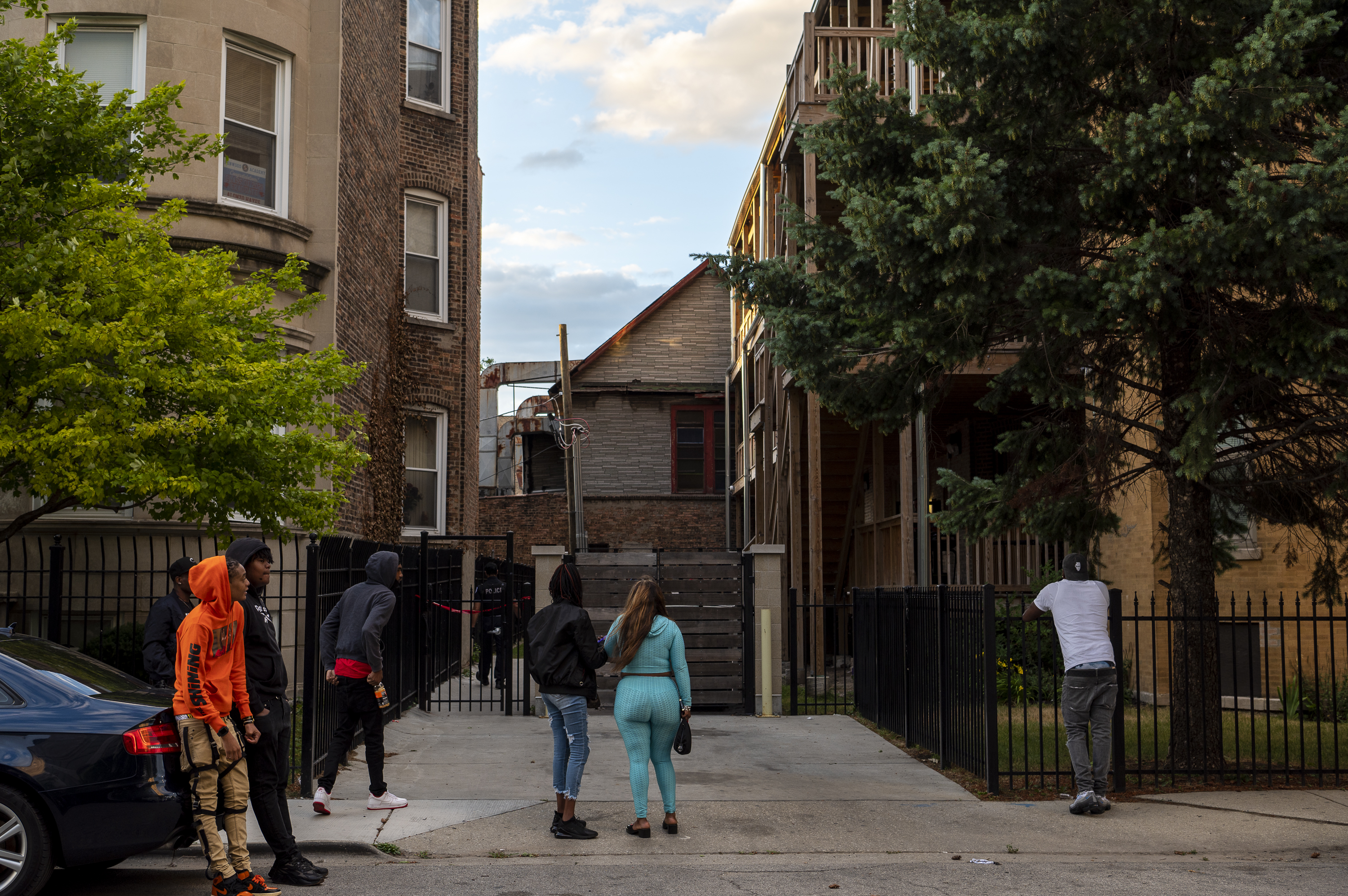 Onlookers watch as Chicago police work the scene where two people were shot and killed in the 6300 block of South Kimbark Avenue, in the Woodlawn neighborhood, Monday, June 21, 2021.