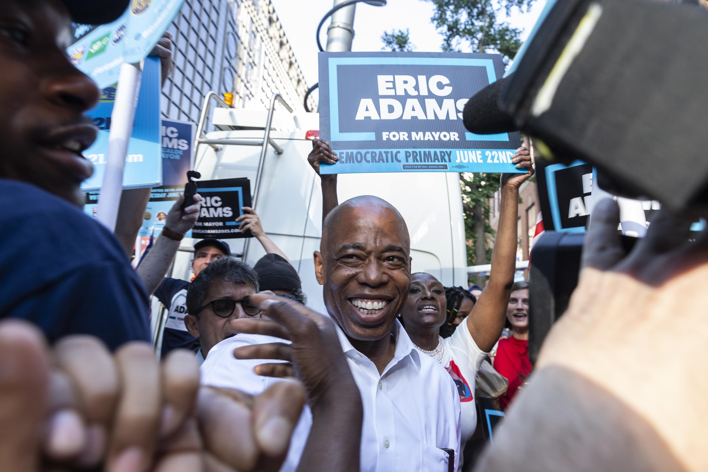 Eric Adams walking through a crowd smiling.