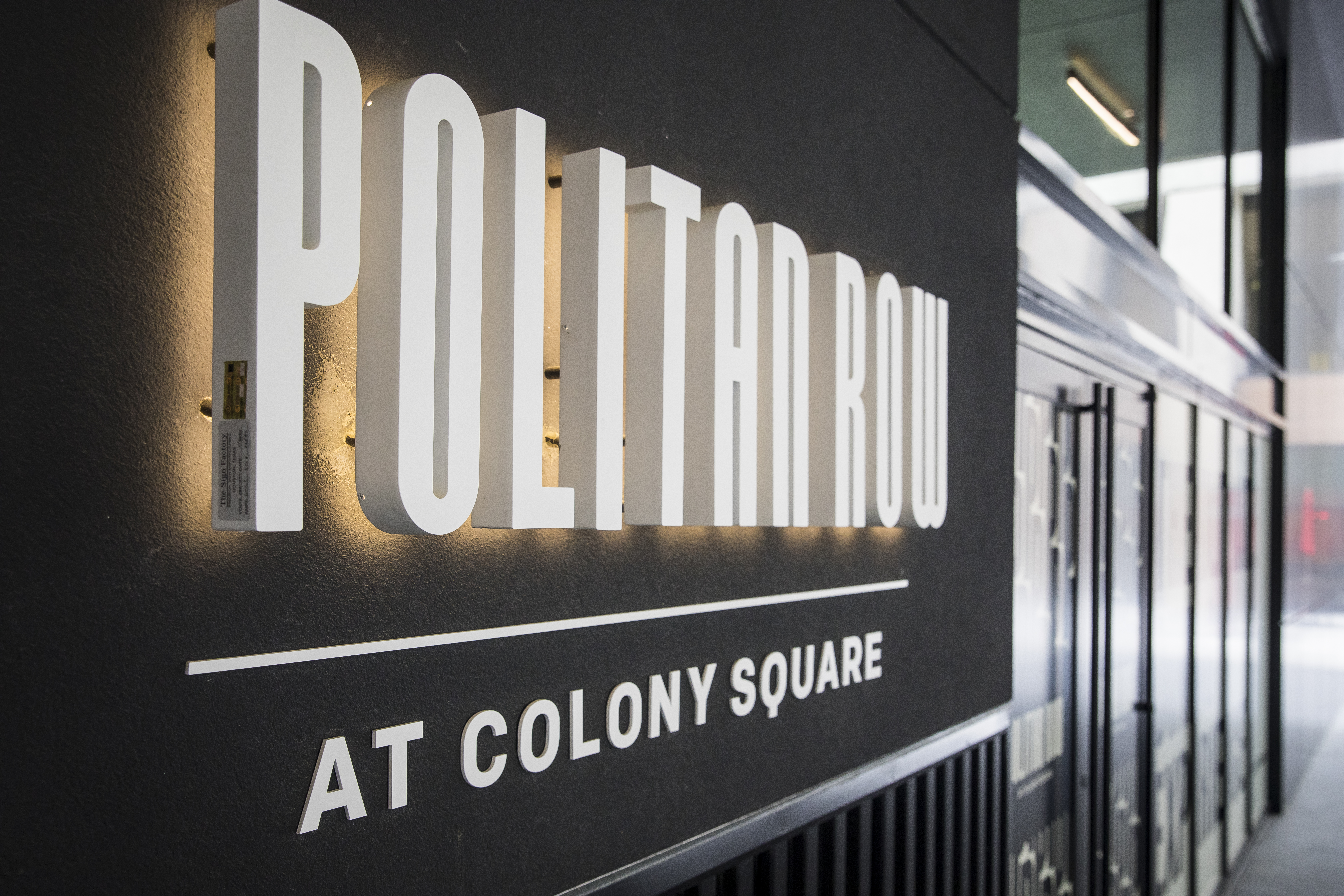 """The lit up white, raised-lettered sign reading """"Politan Row at Colony Square"""" set against a shiny black background in Atlanta"""