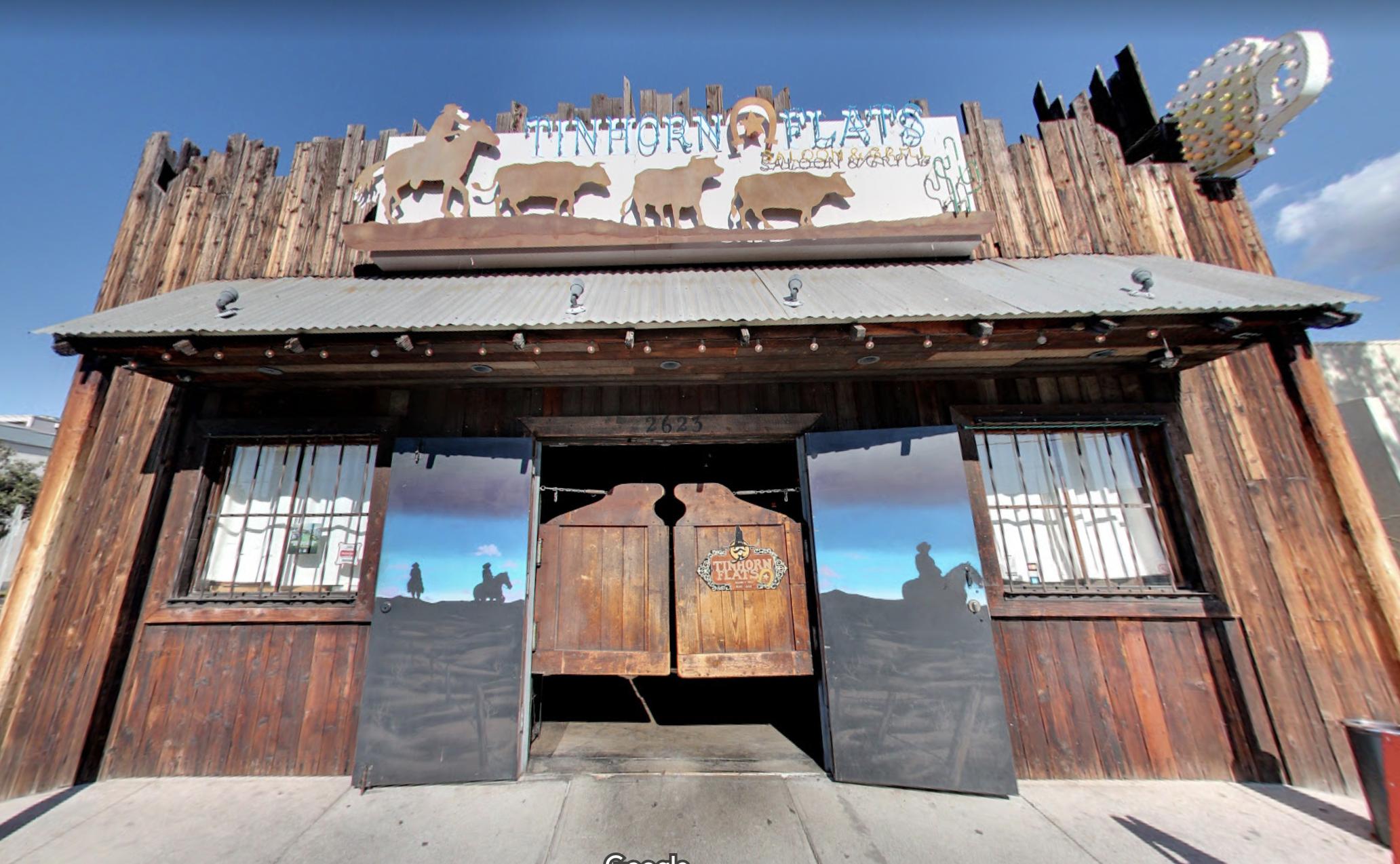 一个西方主题的酒吧从前面,在一个角度,显示了酒吧门和蓝色的天空。