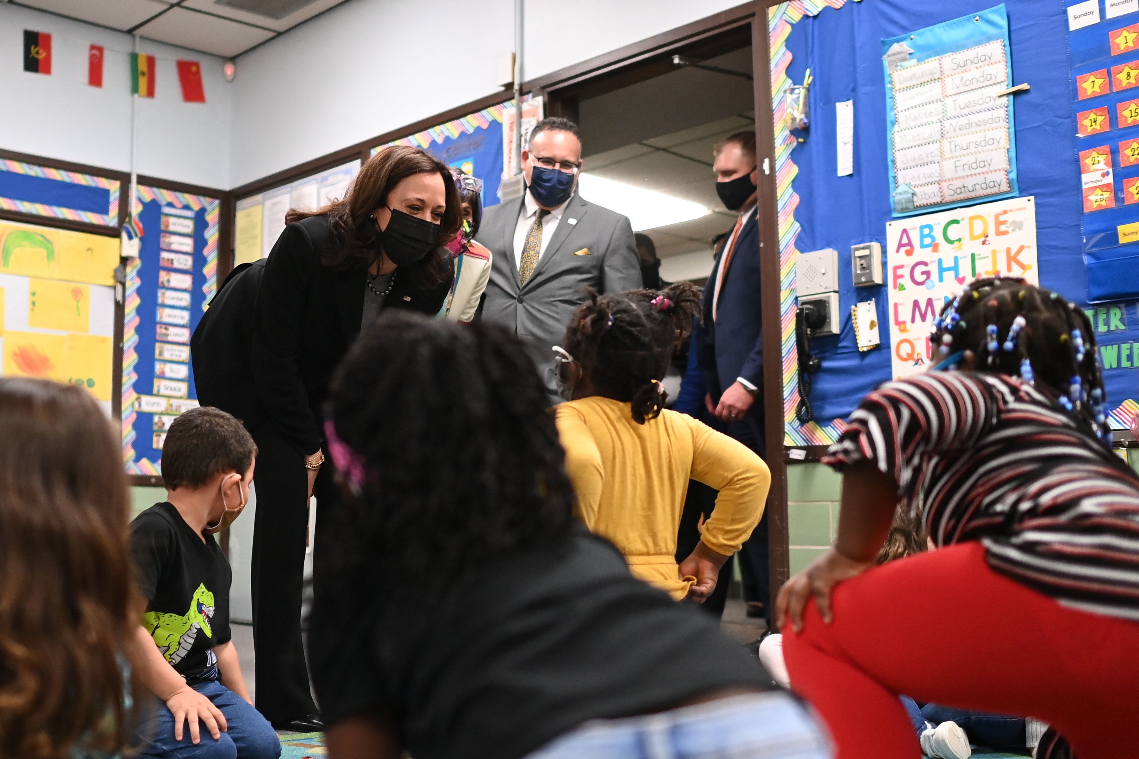 A classroom full of young children greet Vice President Kamala Harris, who is bending over to speak to the kids, as Secretary of Education Miguel Cardona stands behind her.