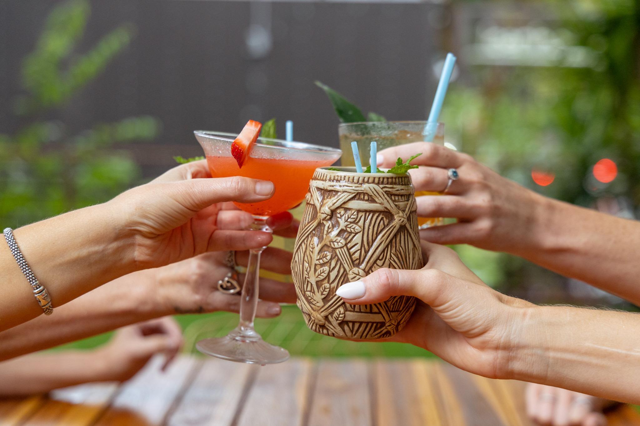 一群鸡尾酒手握在一起,好像在互相敬酒。其中一种鸡尾酒盛在一个看起来像木桶的杯子里。另一种鸡尾酒是红色的,装在马提尼酒杯里。