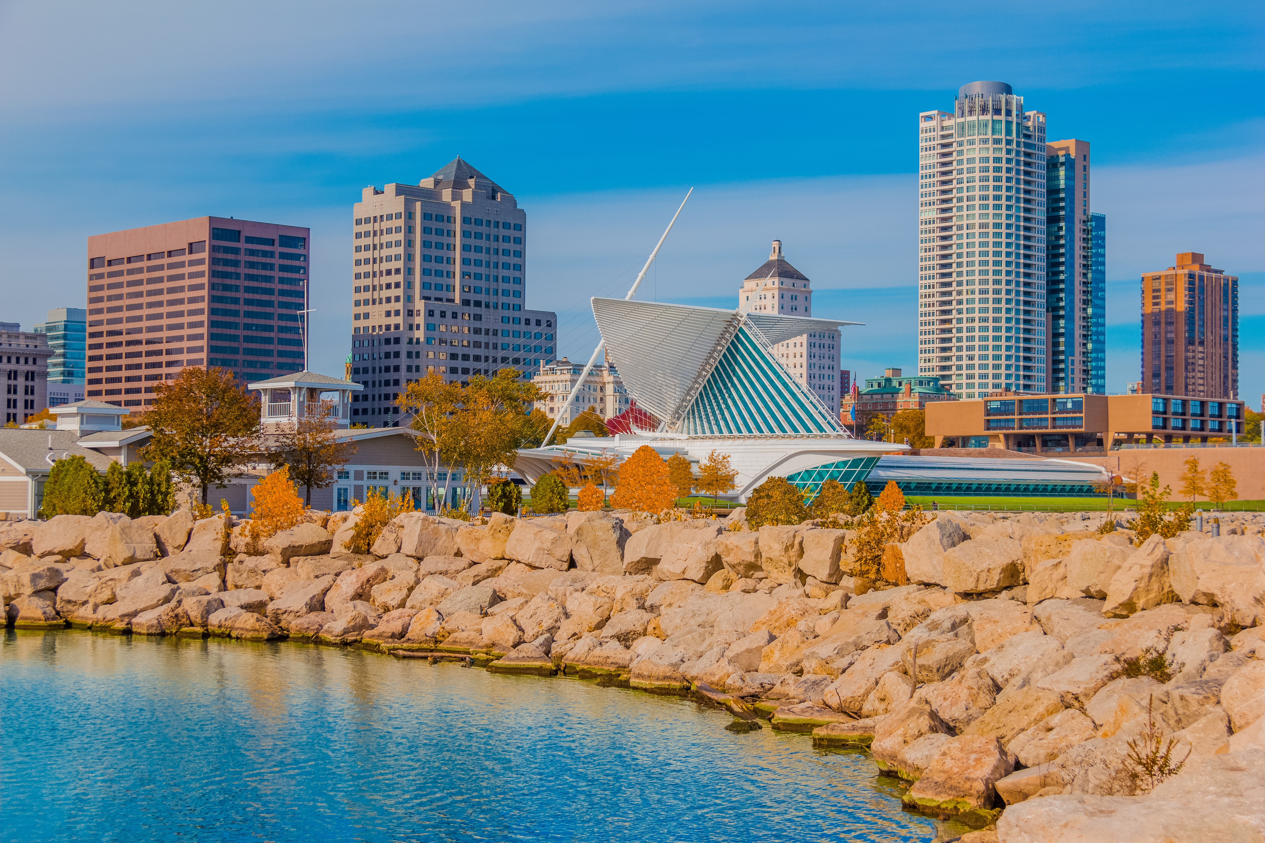 A skyline in Milwaukee with water and rocks.