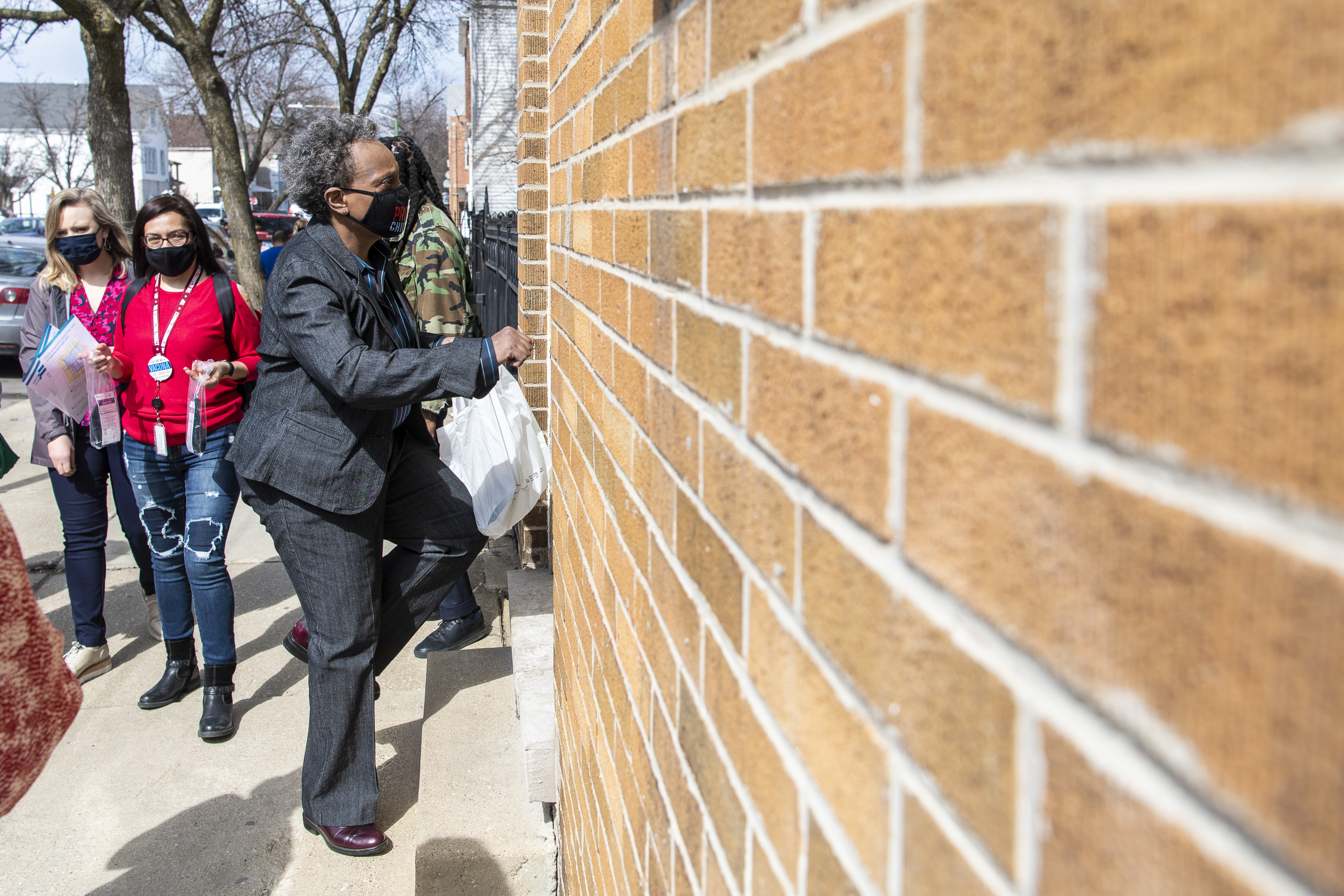 Mayor Lori Lightfoot, pictured in March knocking on the door of a Back of the Yards home to share information about COVID-19 vaccines. The city is now offering in-home vaccinations to all residents 12 or older.
