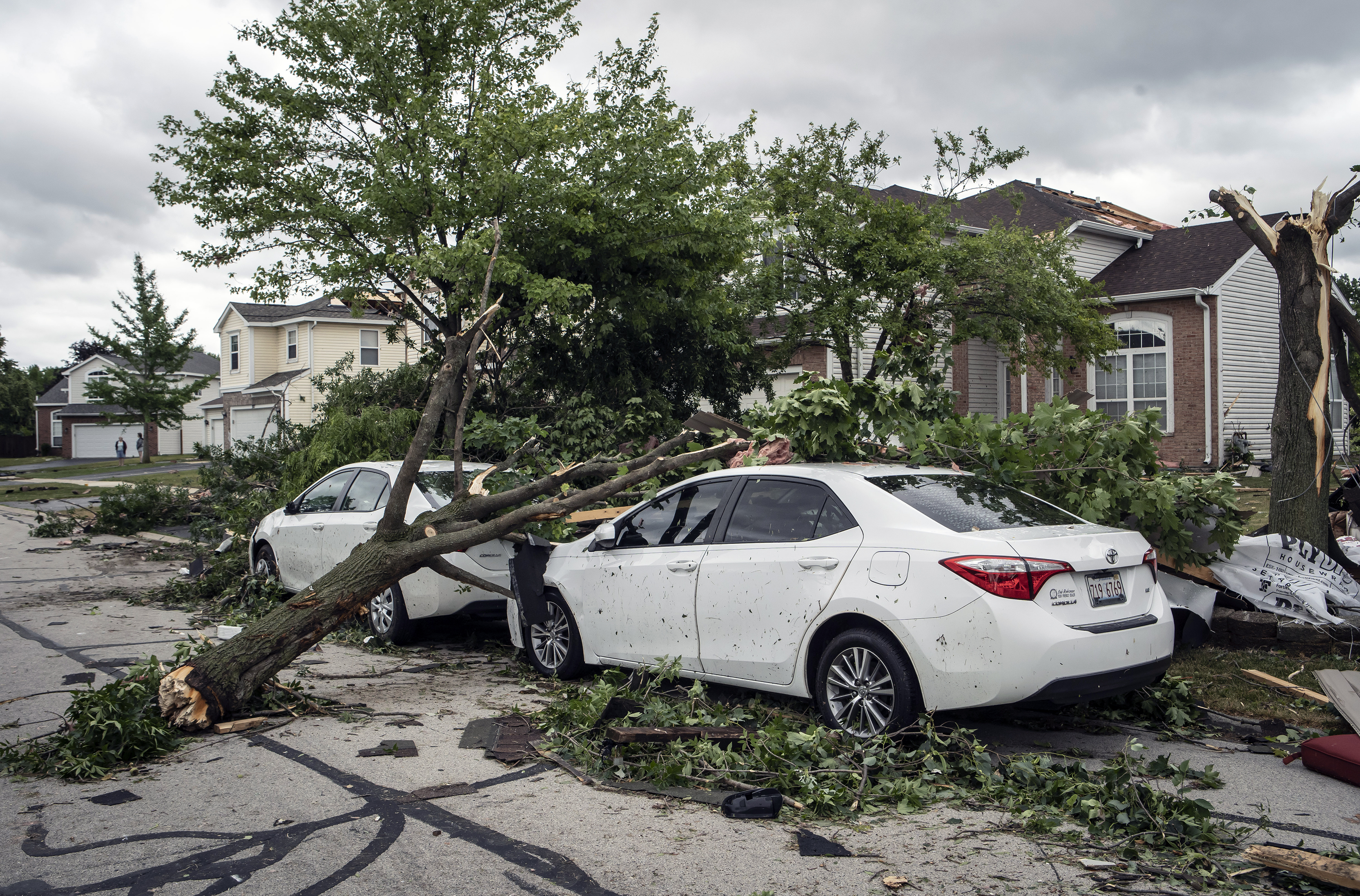 Damaged cars, trees and homes are shown in Naperville, Ill., Monday, June 21, 2021.