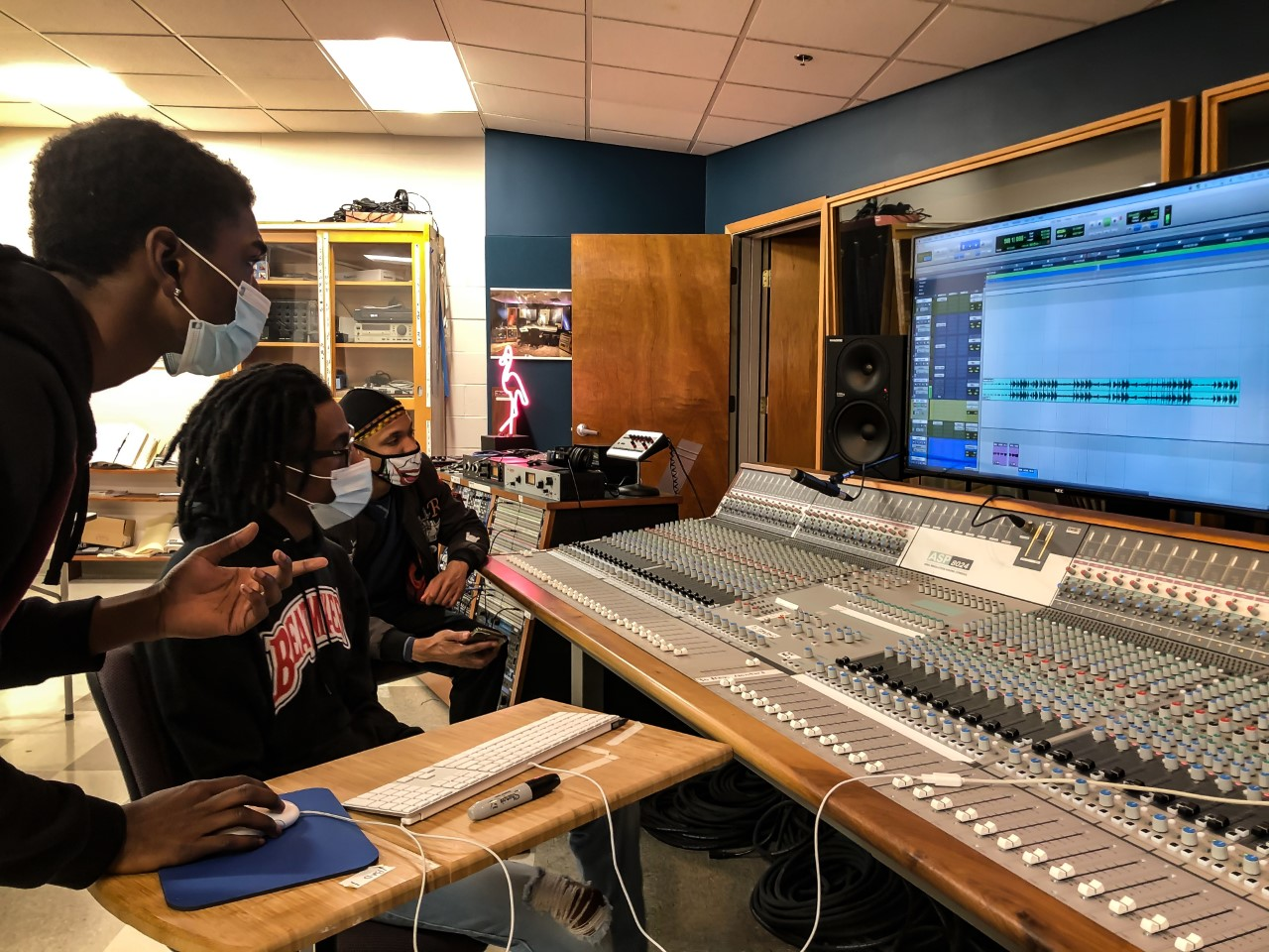 Three Nashville State Community College students, dressed in black sweatshirts and wearing face masks, look at a computer screen while working on a sound board.