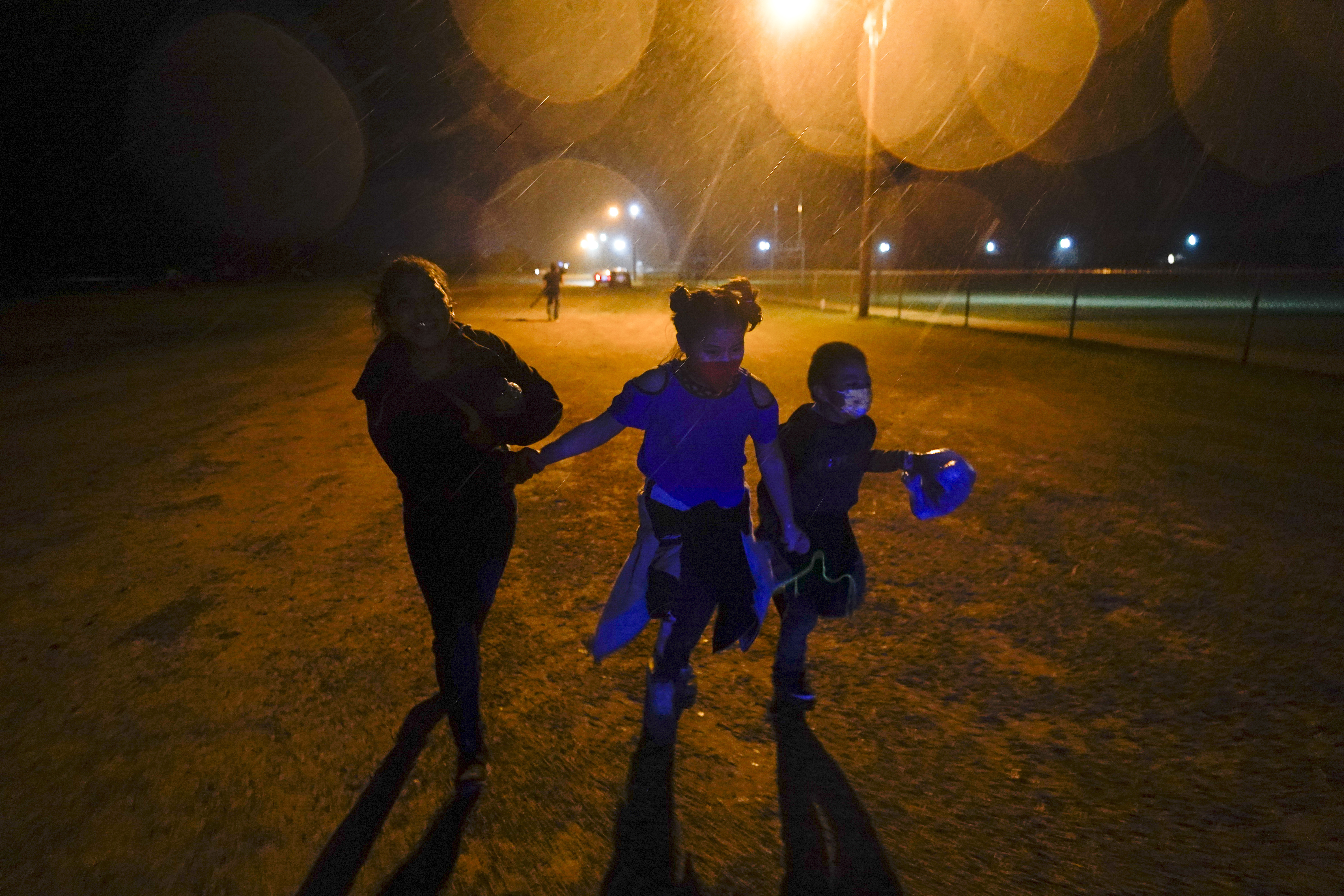 Three young migrant children hold hands as they run in the rain at an intake area after turning themselves in upon crossing the U.S.-Mexico border in Roma, Texas.