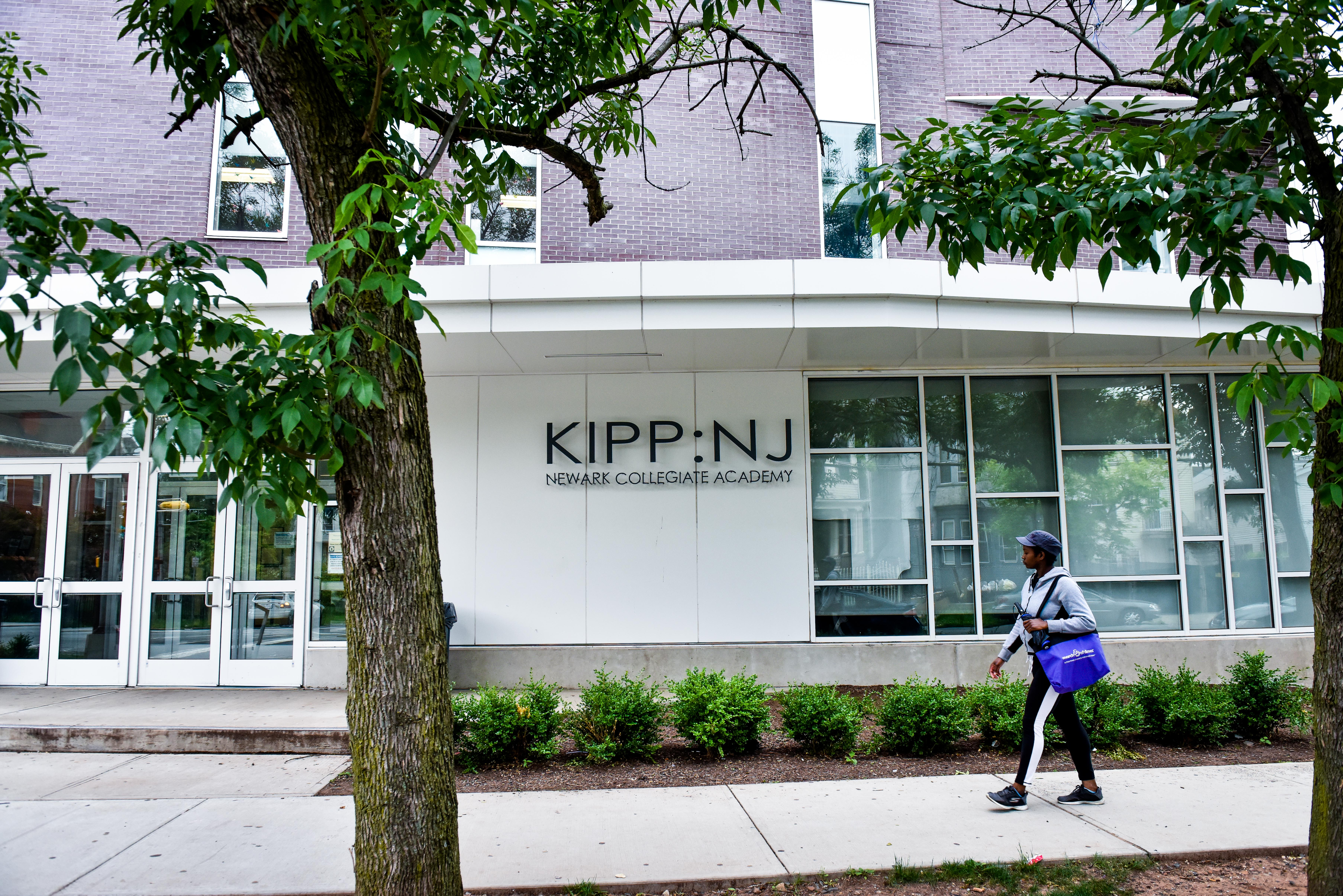 A student wearing a cap and carrying a blue tote bag walks on a walkway in front of the KIPP-NJ building.
