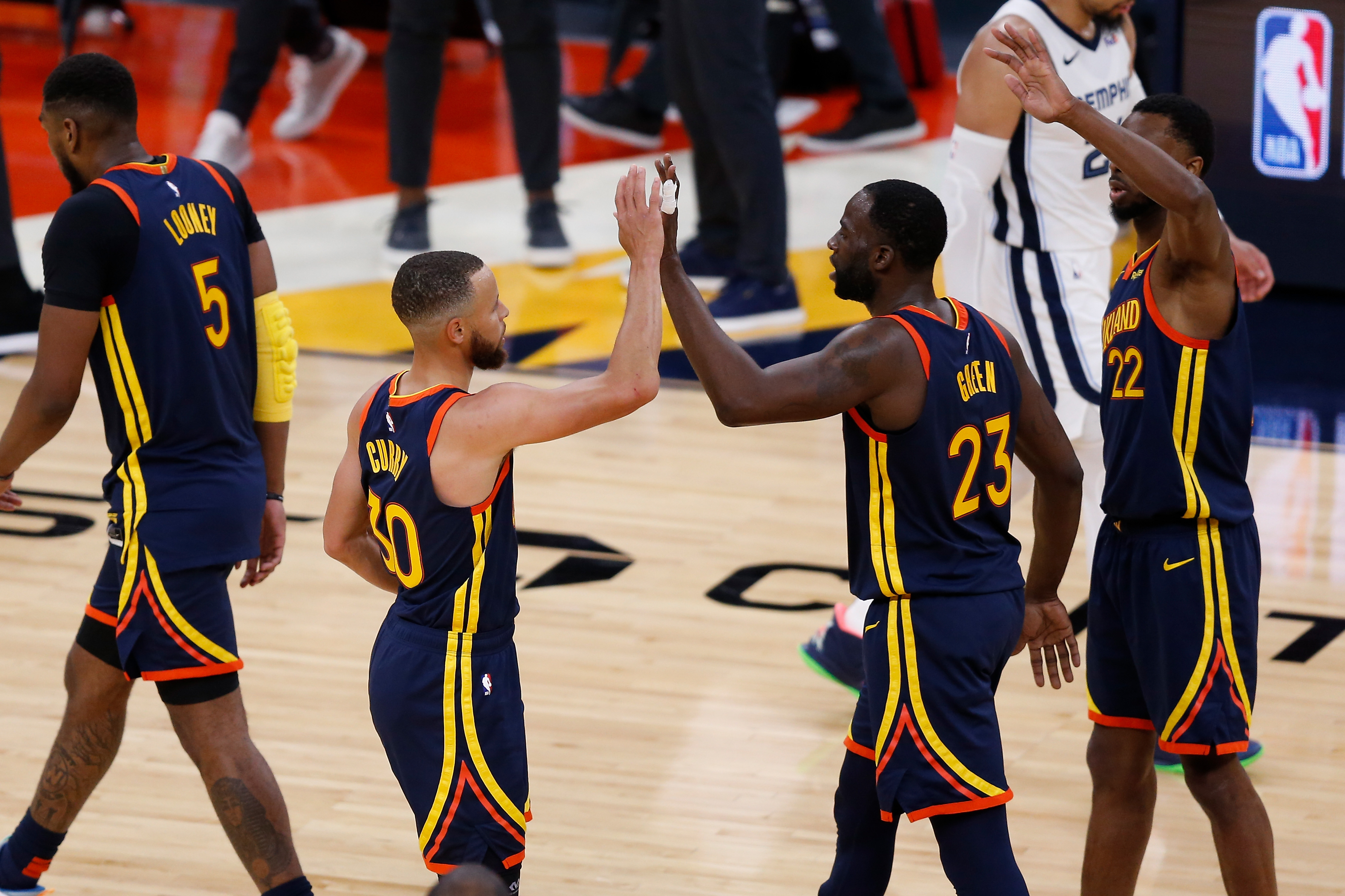 Stephen Curry of the Golden State Warriors celebrates with Draymond Green and Andrew Wiggins during the NBA Play-In Tournament game against the Memphis Grizzlies at Chase Center on May 21, 2021 in San Francisco, California.