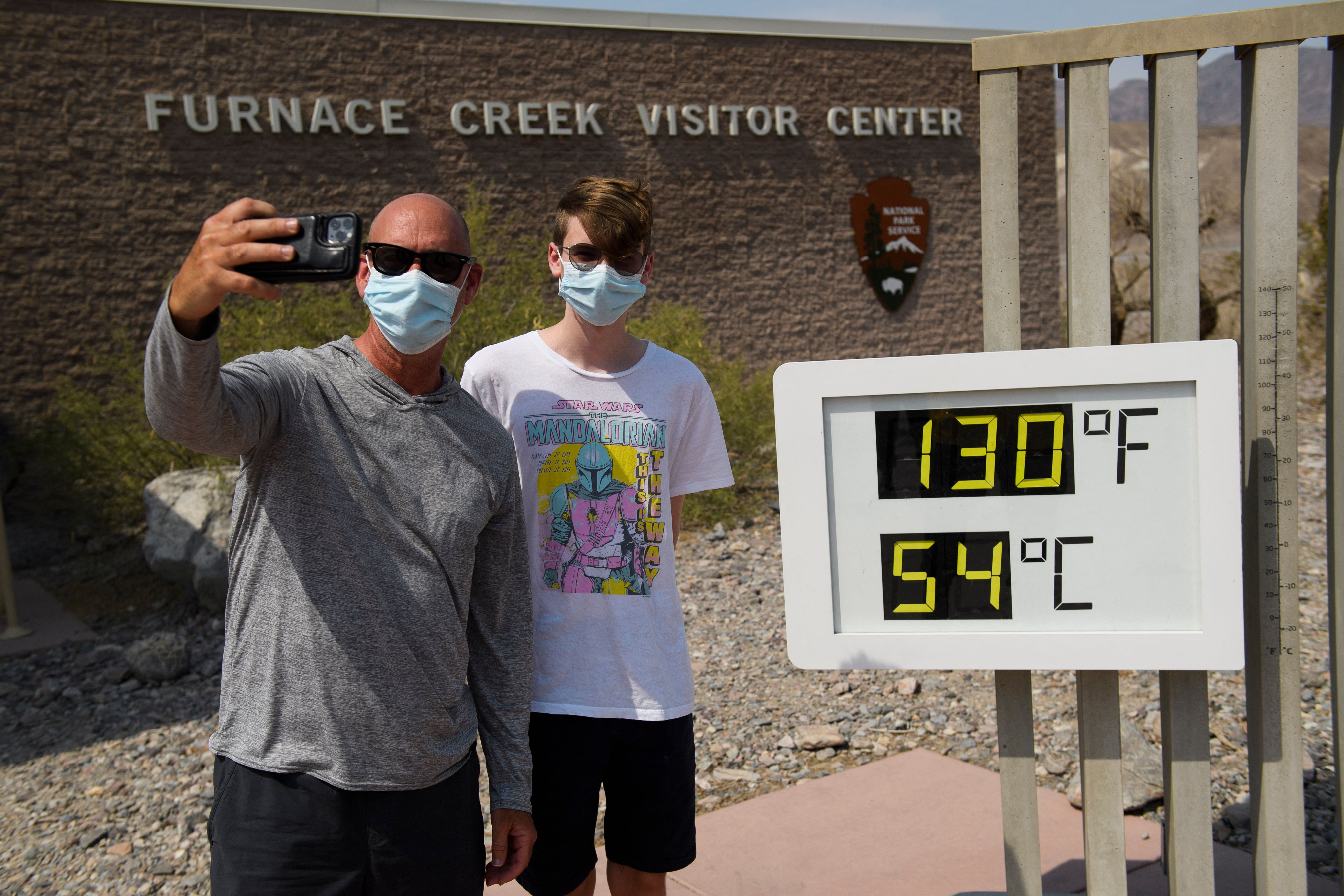 Tourists on a road trip from Texas take pictures with a thermometer displaying temperatures of 130 Degrees Fahrenheit (54 Degrees Celsius) at the Furnace Creek Visitor Center at Death Valley National Park in June 17, 2021.