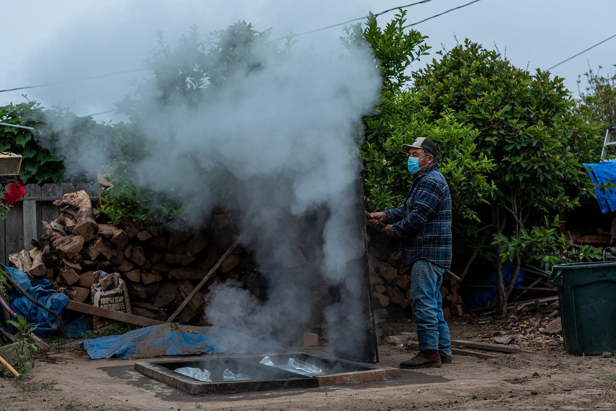 Francisco Bautista opens the pit in his family's backyard in Santa Maria, California.