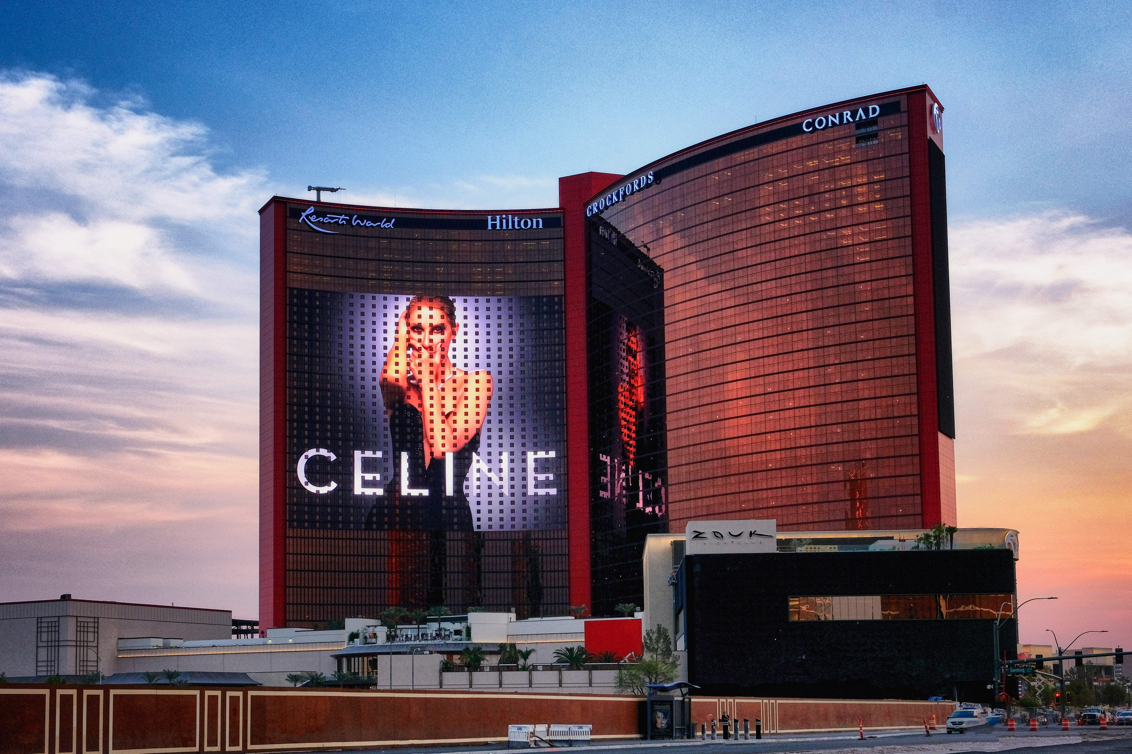 A hotel at dusk with a giant photo of Celine Dioon on one tower