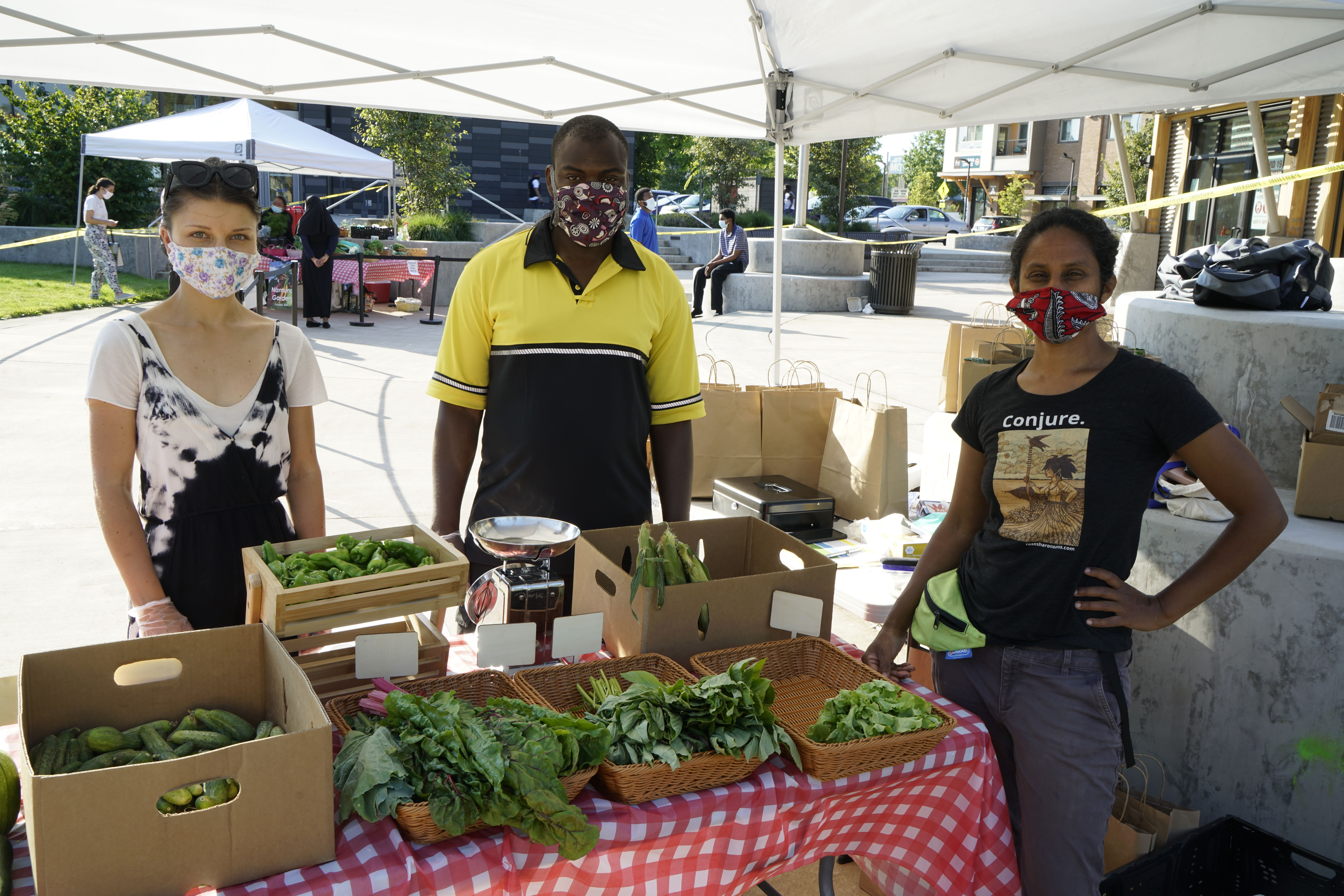 穿面部面具的三个人站立在显示各种叶茂盛绿色蔬菜的桌子