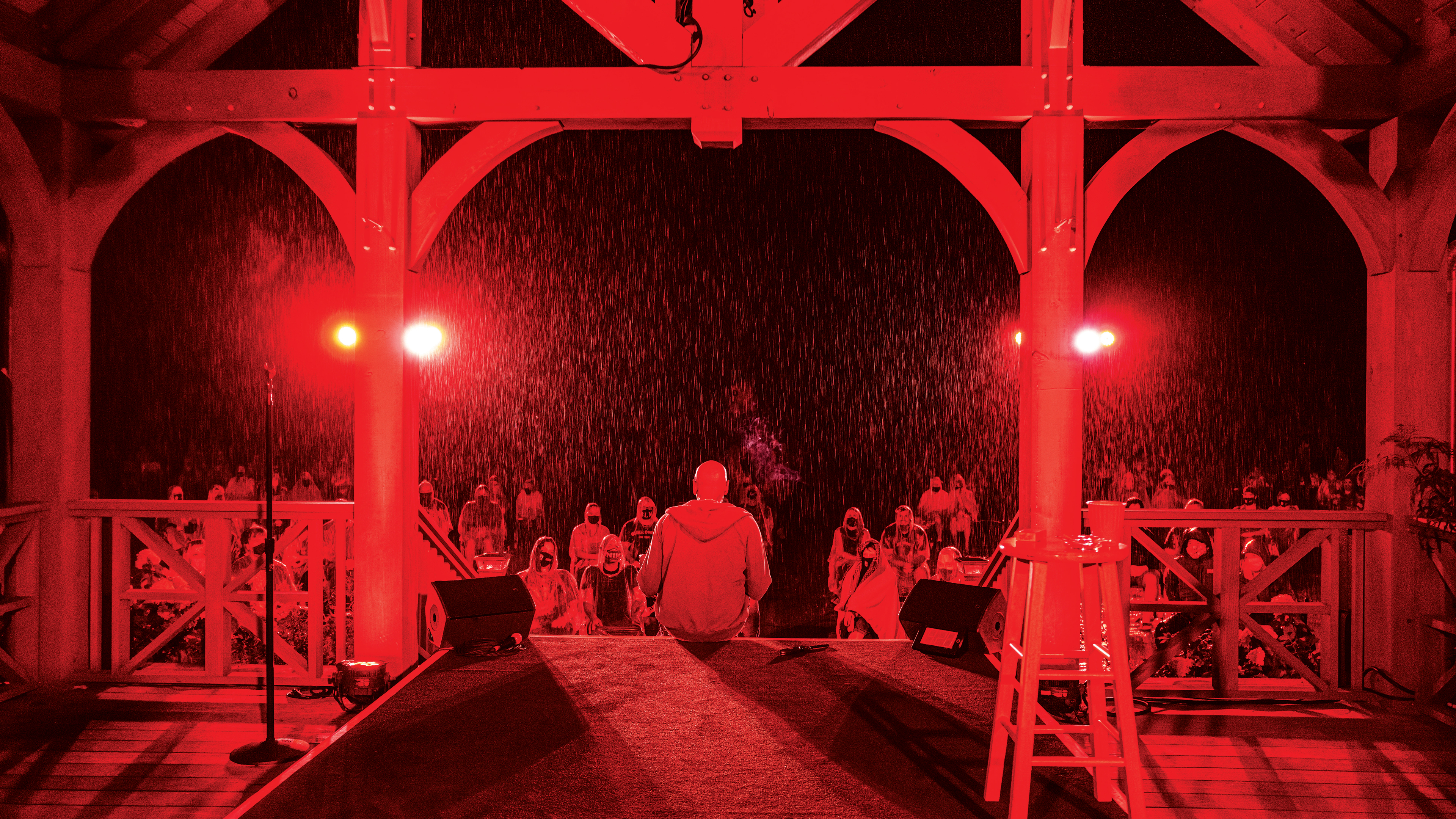 A red-lit view of a comedian sitting on gazebo steps facing a crowd in the rain.