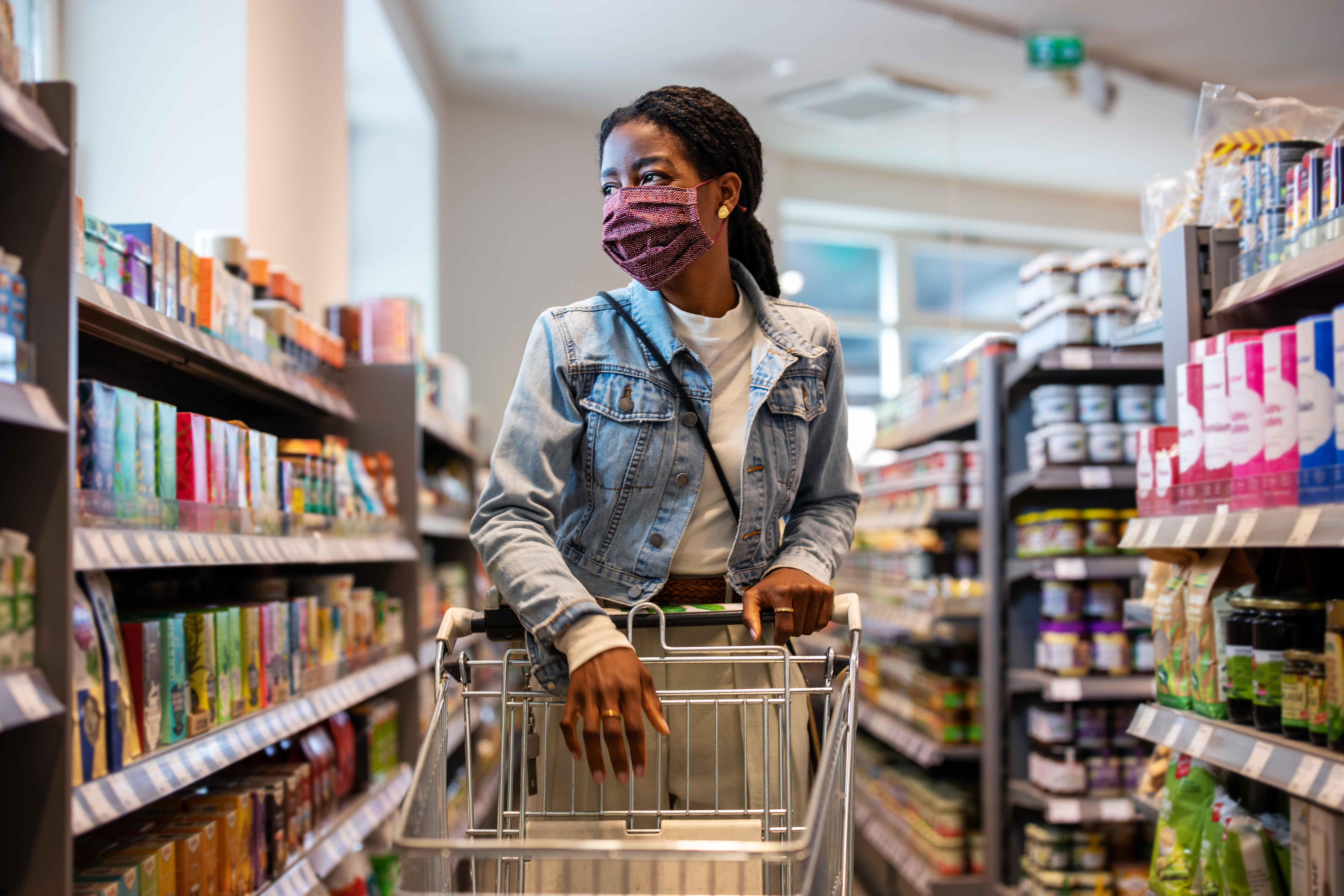 A woman wearing a face mask shops in a grocery store.