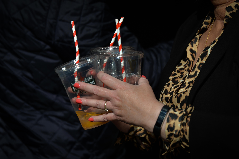 一个穿着豹纹衬衫的人拿着三个装满塑料啤酒的杯子和红白相间的吸管